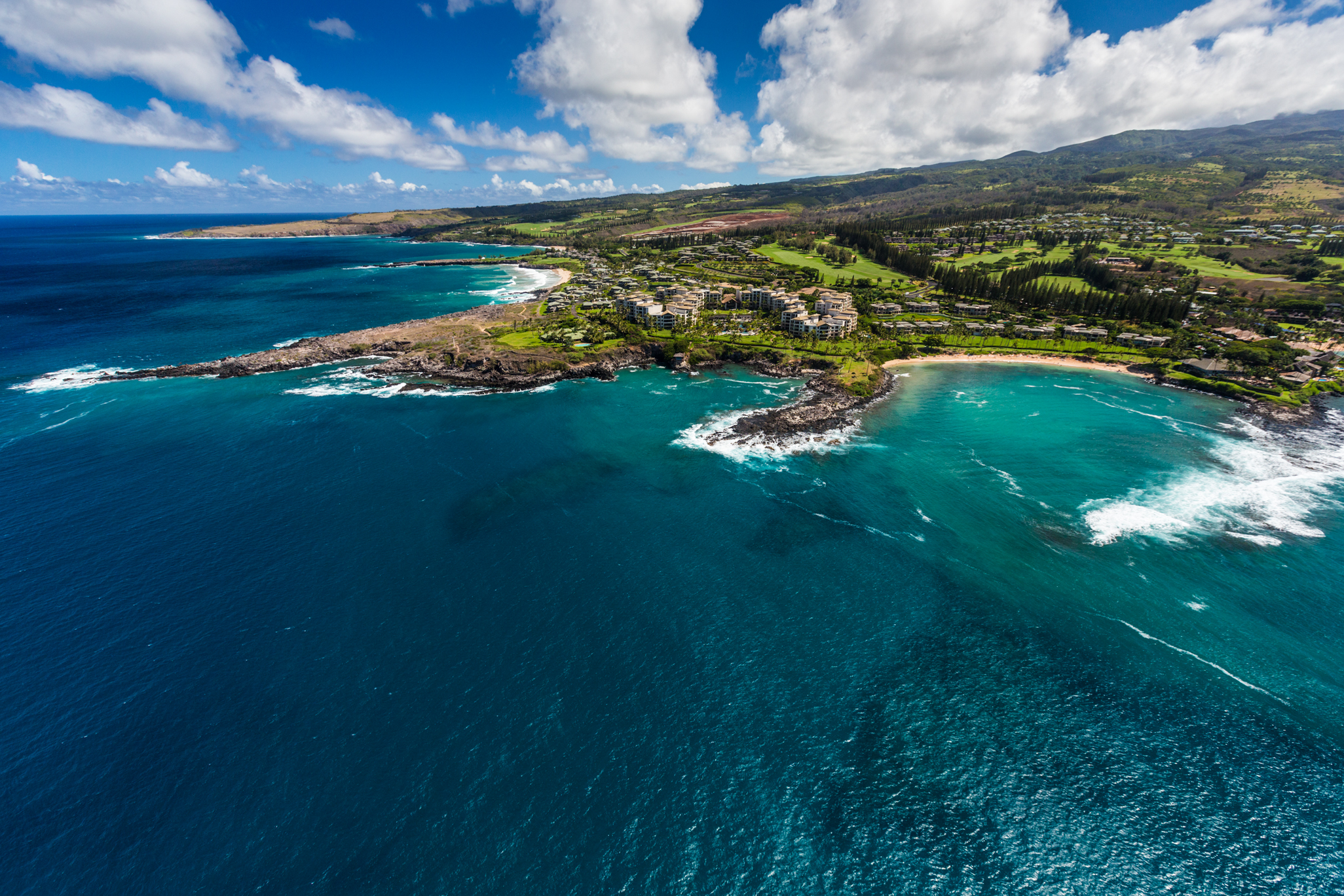 This aerial view of the Maui coastline shows off the shades of ocean and rocky beaches you can see on an adventurous helicopter ride, one of the best Maui adventures.