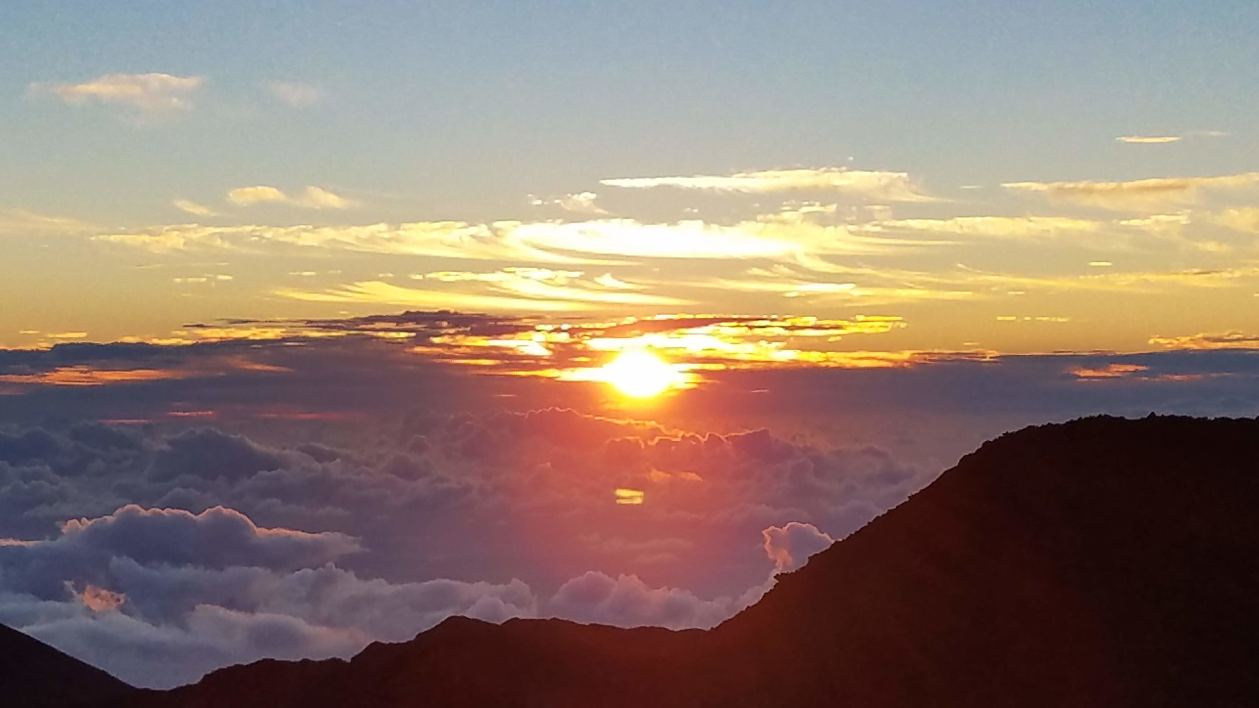 The Haleakala National Park sunrise peaks above the clouds around the Haleakala summit.
