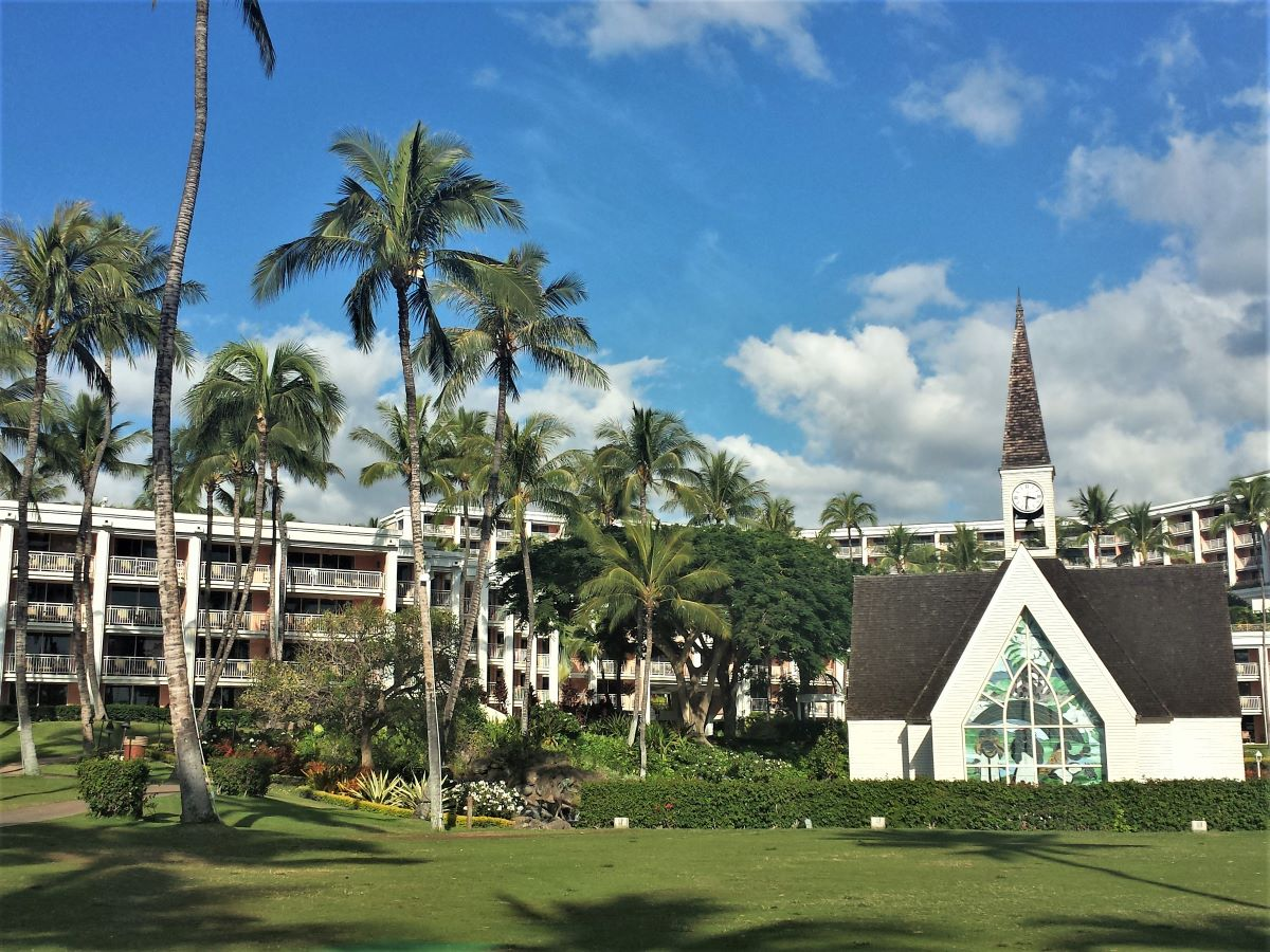 A resort surrounded by palm trees with a chapel on the lawn in Wailea is one of the best places to stay in Maui.