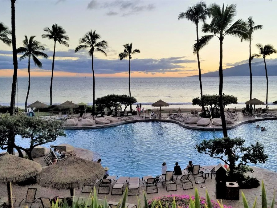 This Maui beach resort in Kaanapali has a big pool surrounded by palms and lounge chairs overlooking the ocean at sunset.