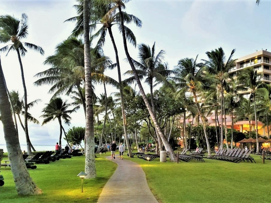 West Maui hotels on the beach with an oceanfront walkway running between palm-tree filled lawns.