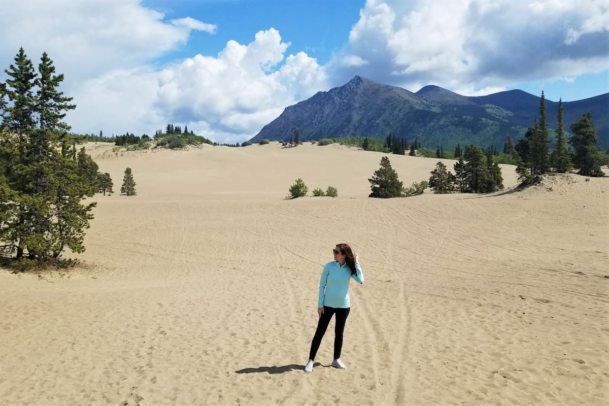 Girl in blue top stands in the middle of the sandy Carcross Desert in Canada.
