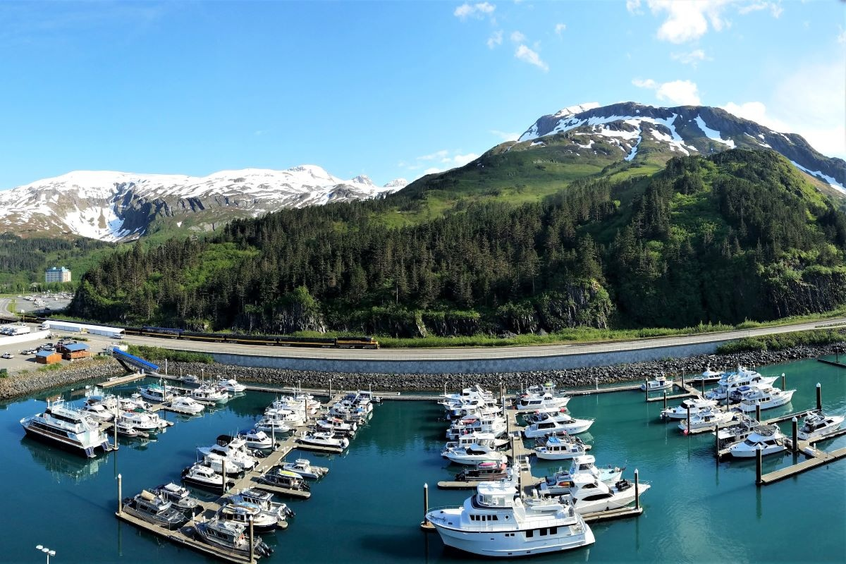 An Alaska trip itinerary that includes a cruise means scenery like this port filled with small boats backed by a mountain and railroad.