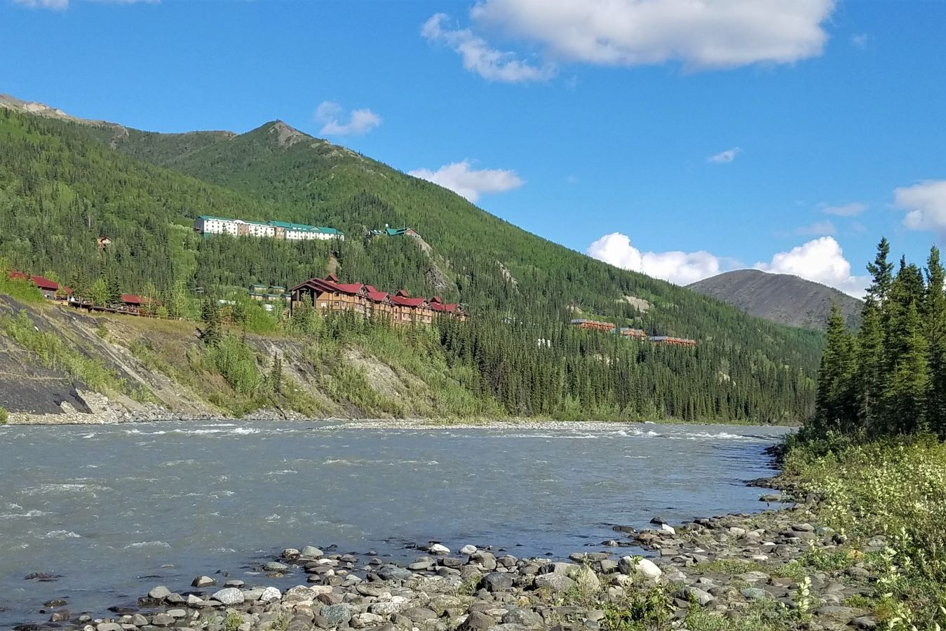 River by Denali National Park in Alaska with hotels on the bluffs and green trees all around.