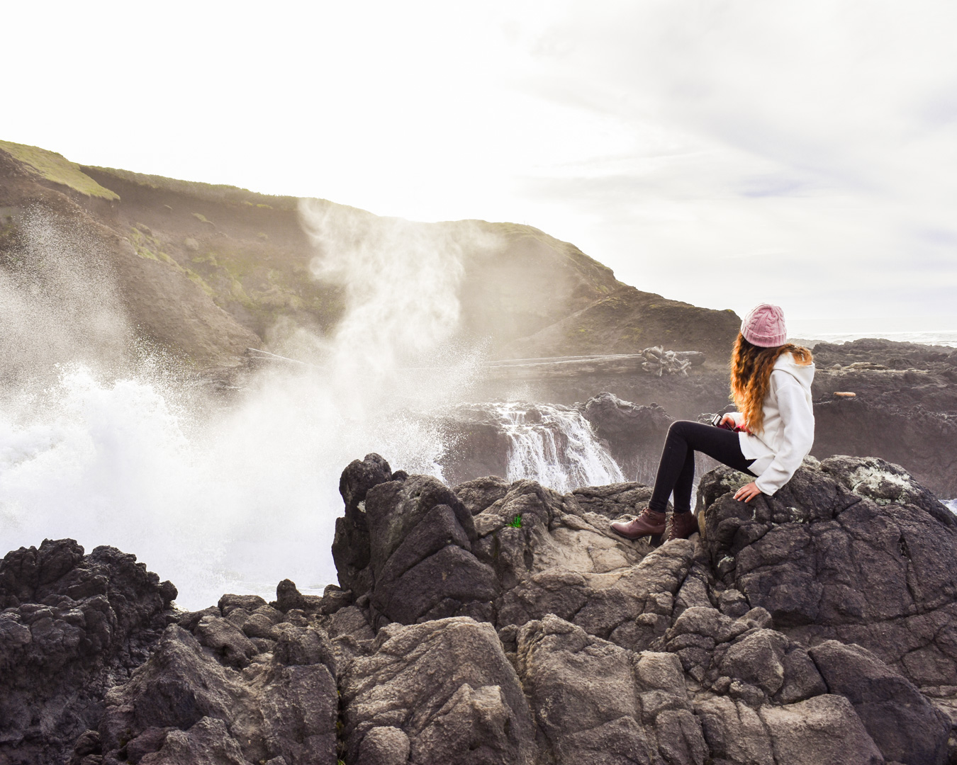 Girl in pink hat sits on black rocks on the coast of Yachats, Oregon, as waves crash onto the shore.
