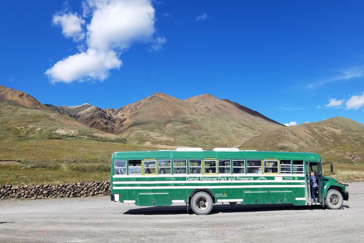 A green school bus used for Denali bus tours with mountains in the background.