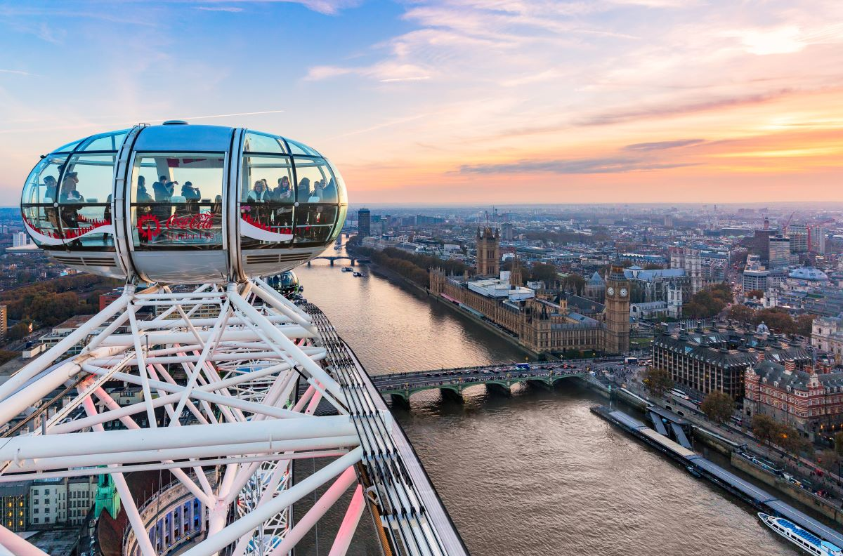 Closeup of a glass pod on the London Eye wheel elevated high above the river with Palaces of Westminster on the right. This sunset scene on the Thames River is part of a London itinerary for 4 days in the city.