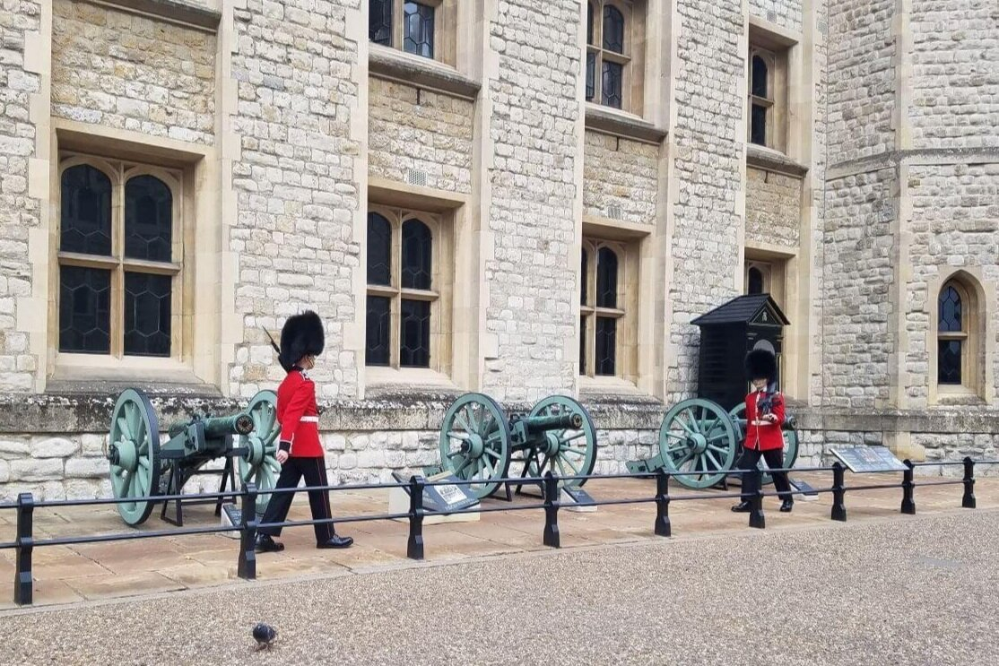 Two soldiers in red coats and black helmets march in front of canyons and a castle wall, one of the London palaces recommended on this London bucket list.