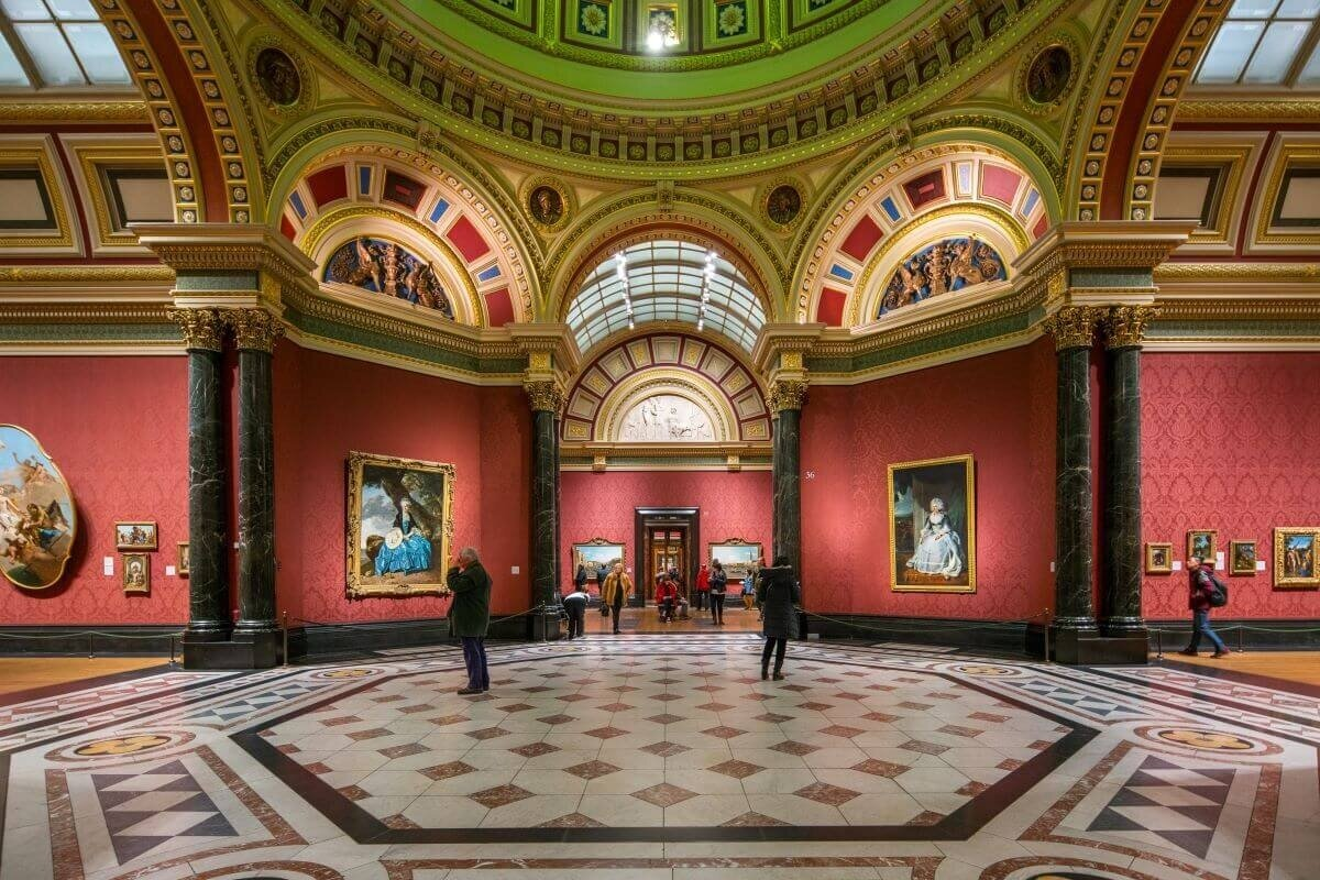 Fun things to do in London include visiting museums like this one, the National Gallery with portraits in gold frames hung on red walls in a long hallway full of people.