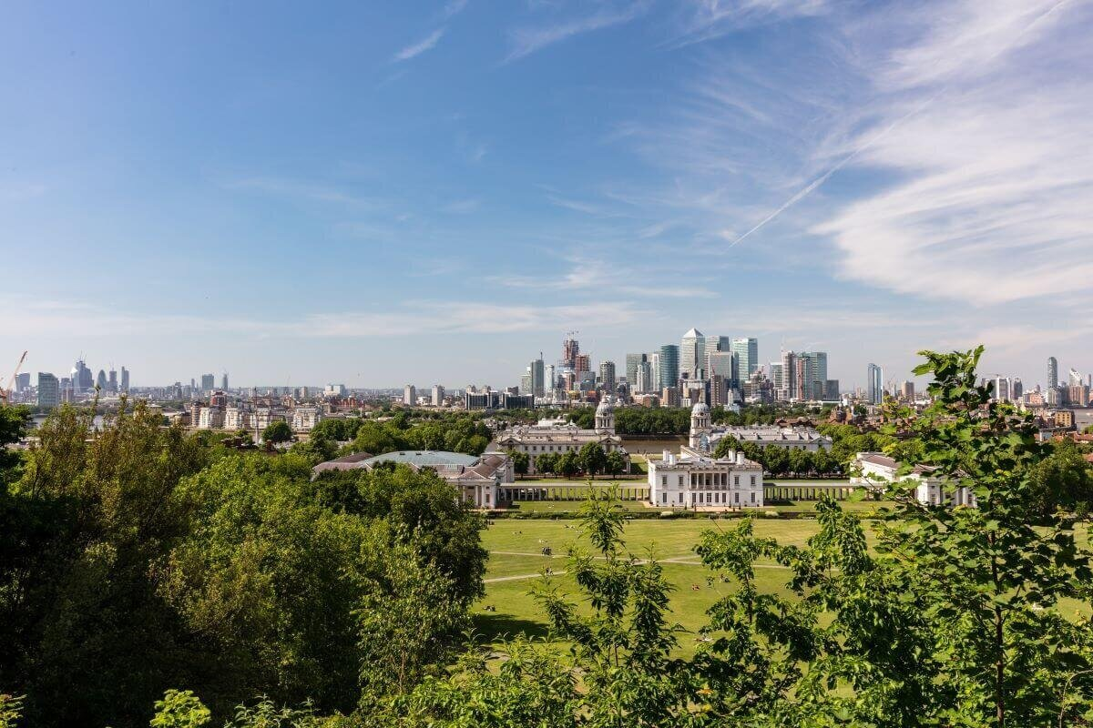 A hilltop view of green lawns surrounded by trees with a city skyline in the background at Greenwich park, one of the best London gardens.