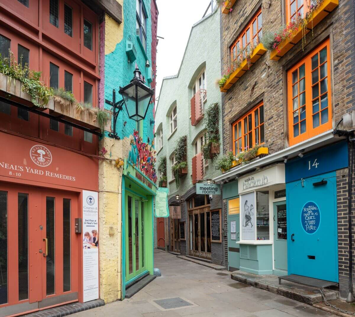 This London shopping street is a narrow alley with colorful storefronts and doors in brick buildings.