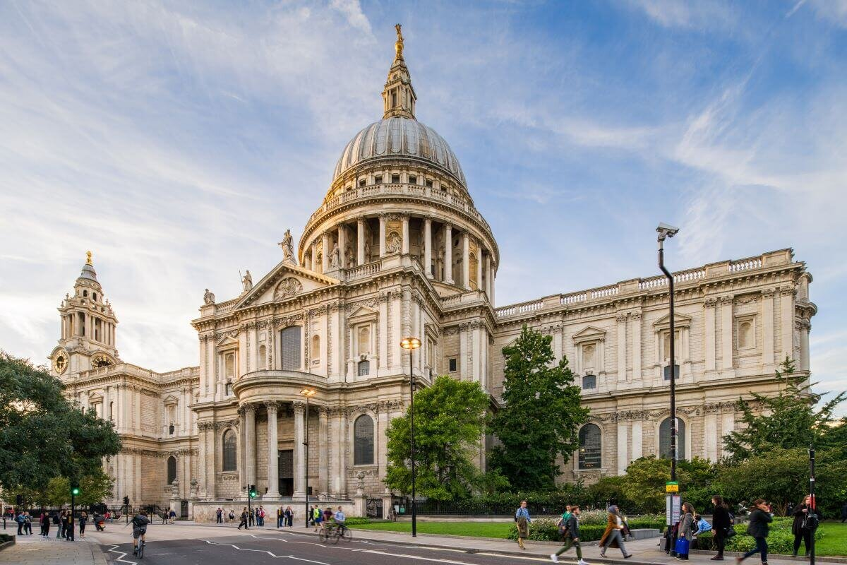Famous London churches include St. Paul's Cathedral, pictured with a towering cupola and pedestrians walking in front.
