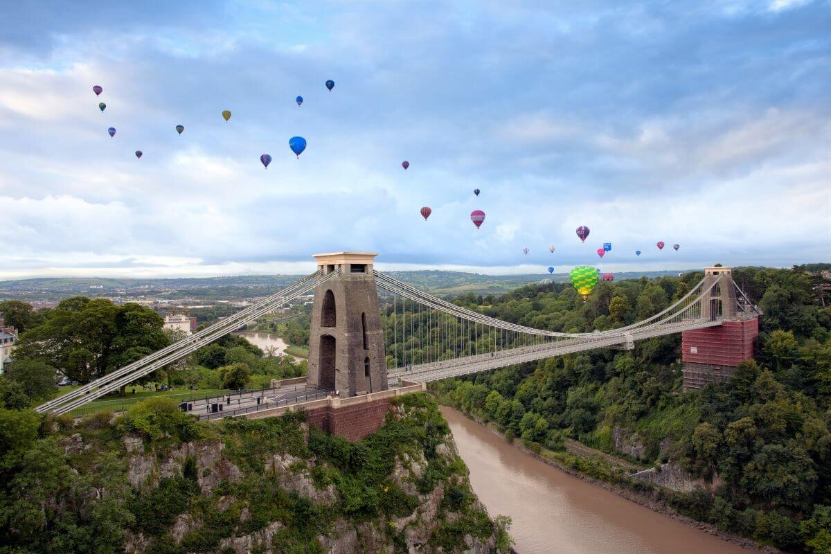 Hot air balloons float over the Clifton Suspension Bridge across a gorge in Bristol, one the best day trips from London.
