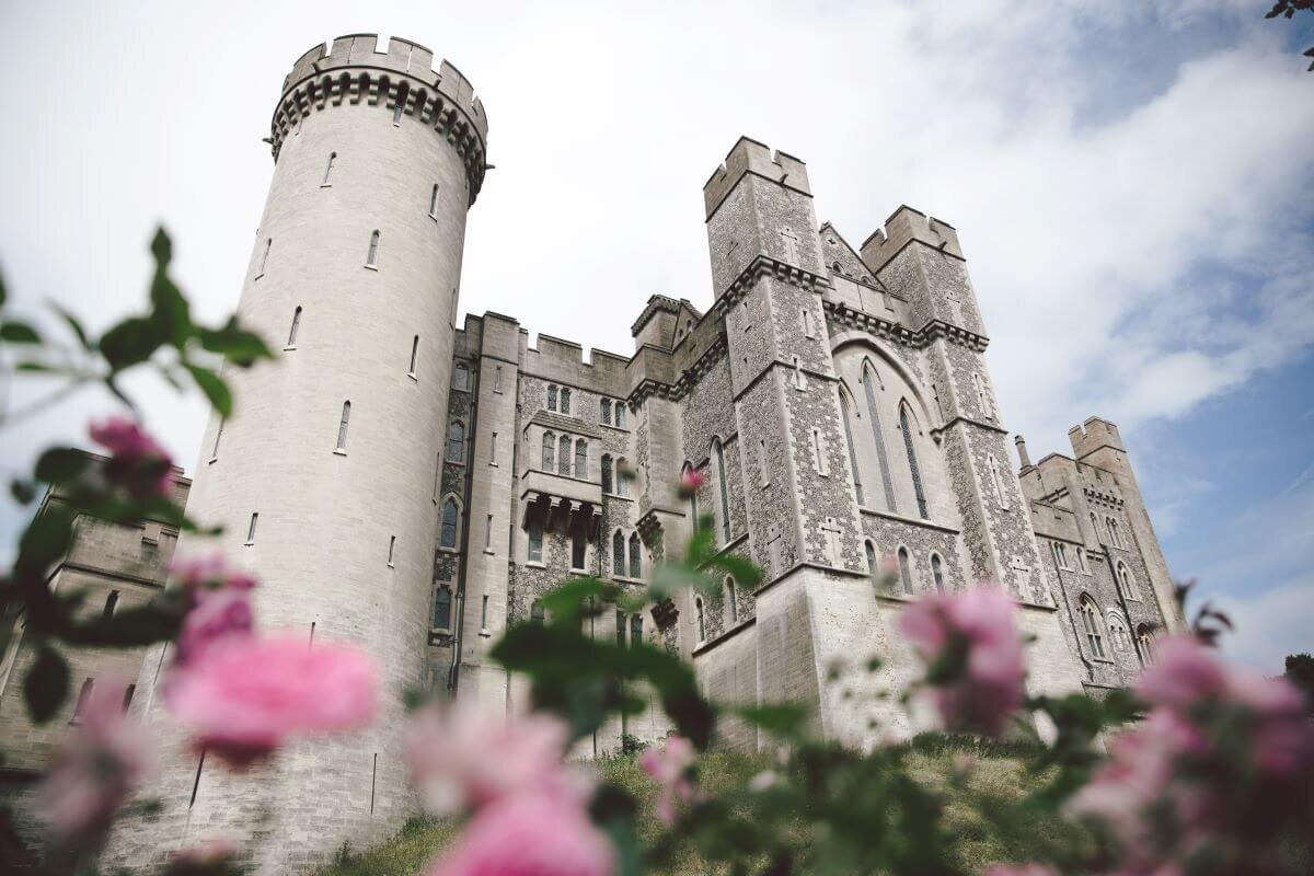 Arundel Castle's front and turret with pink flowers in the foreground under a cloudy blue sky.