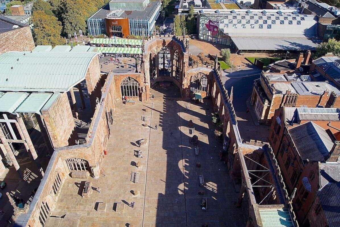 An aerial shot of a the walls of an old cathedral with the top missing and surrounded by buildings in Coventry, a day trip from London.