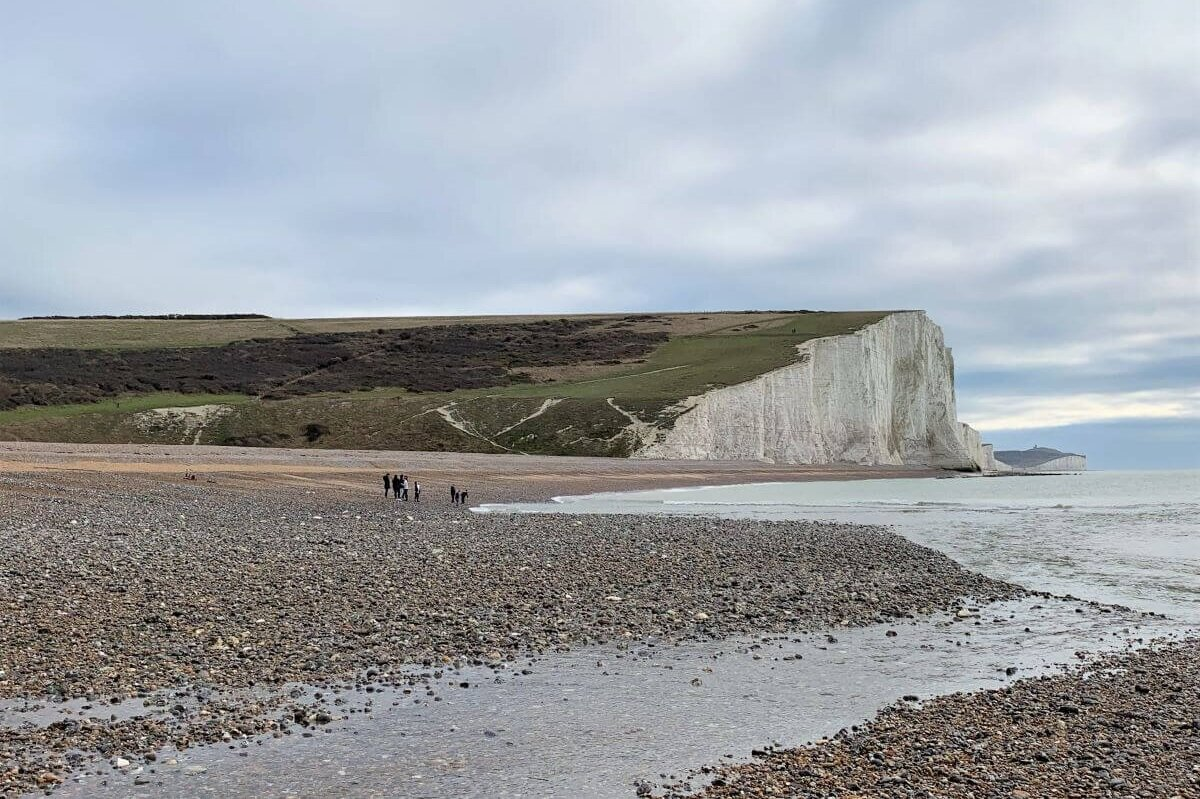 The white Seven Sisters cliffs topped with grass in the background and pebbly shoreline with the waves washing up. The cliffs are part of South Downs National Park.