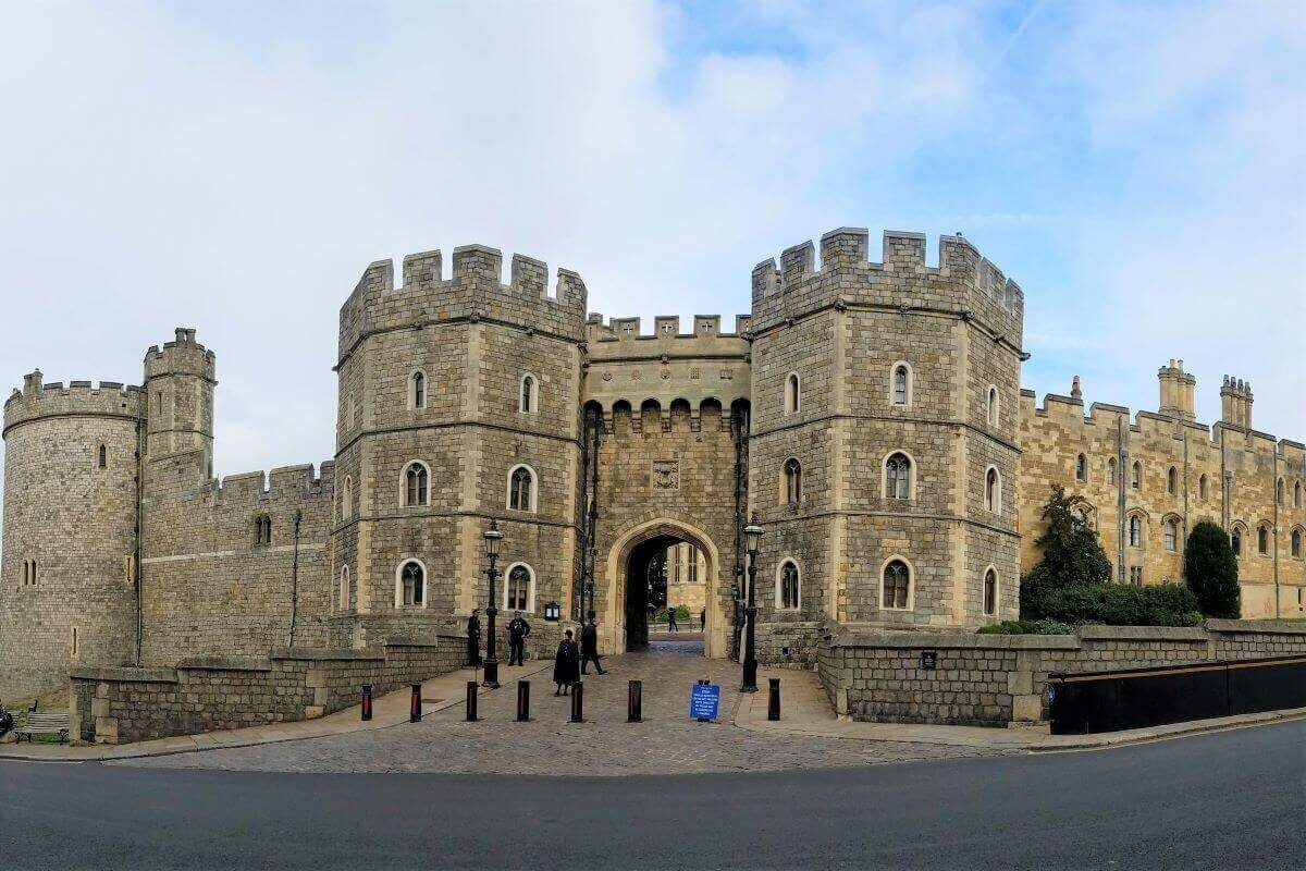 The exterior of Windsor Castle with two stone turrets and an entry gate. London to Windsor Castle is a popular day trip from the city.