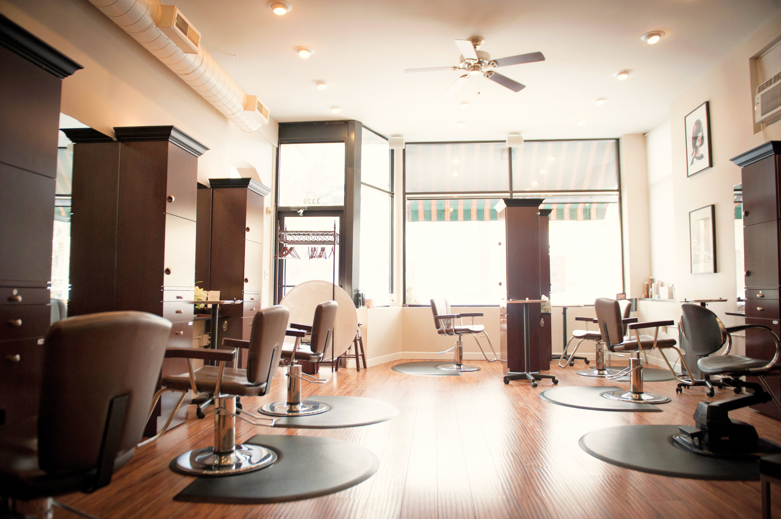 Salon La Terre hair stations with brown chairs and large windows