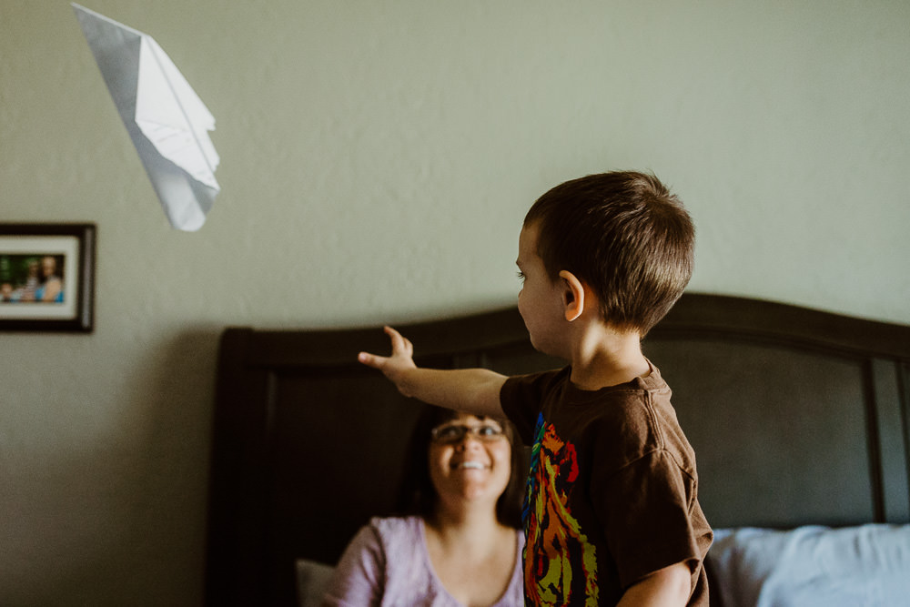 documentary lifestyle photo session mother and child in bed flying paper planes Ore Adesina Oklahoma City