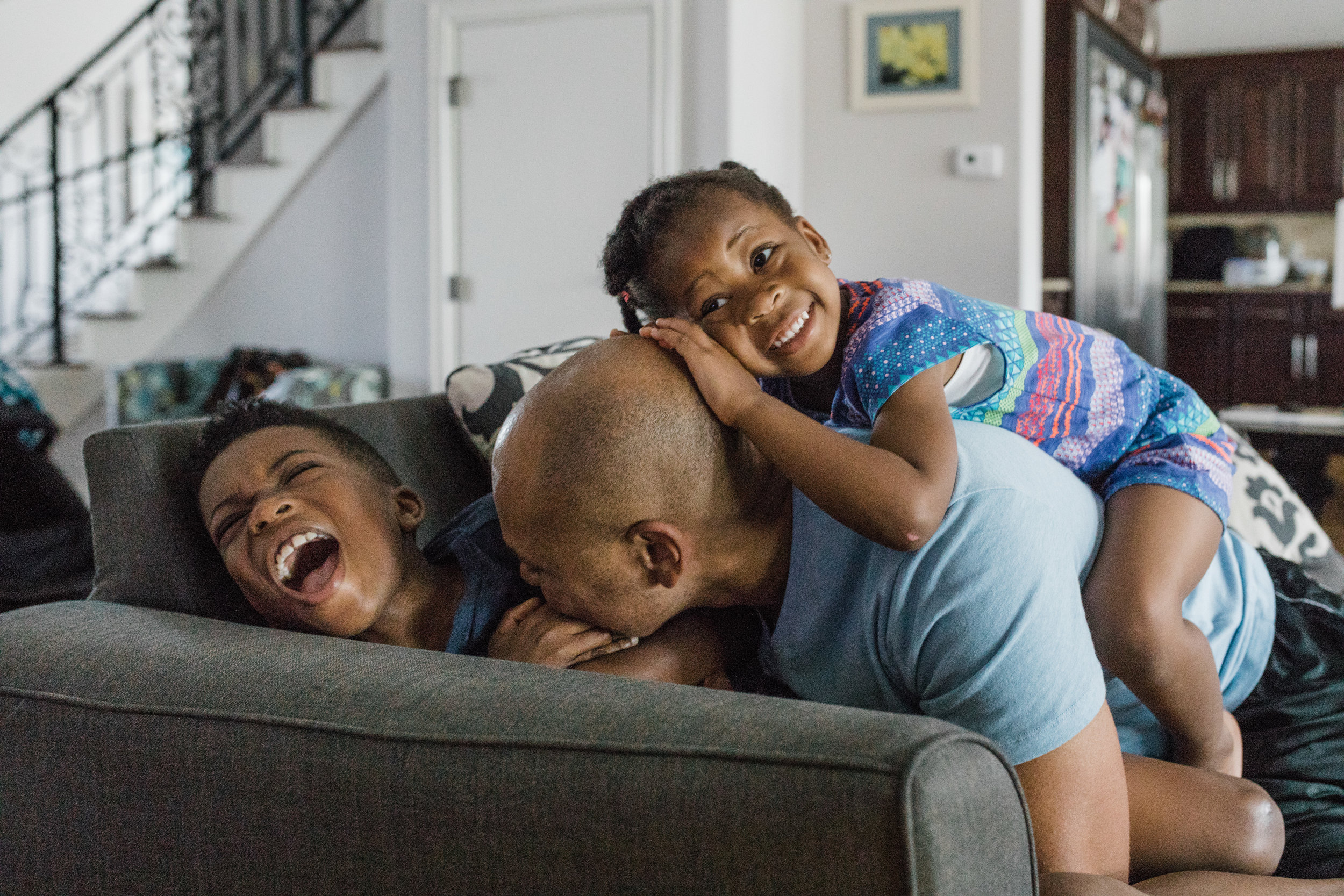 documentary lifestyle family photo session kids climbing on dad on couch Ore Adesina Photography Oklahoma City