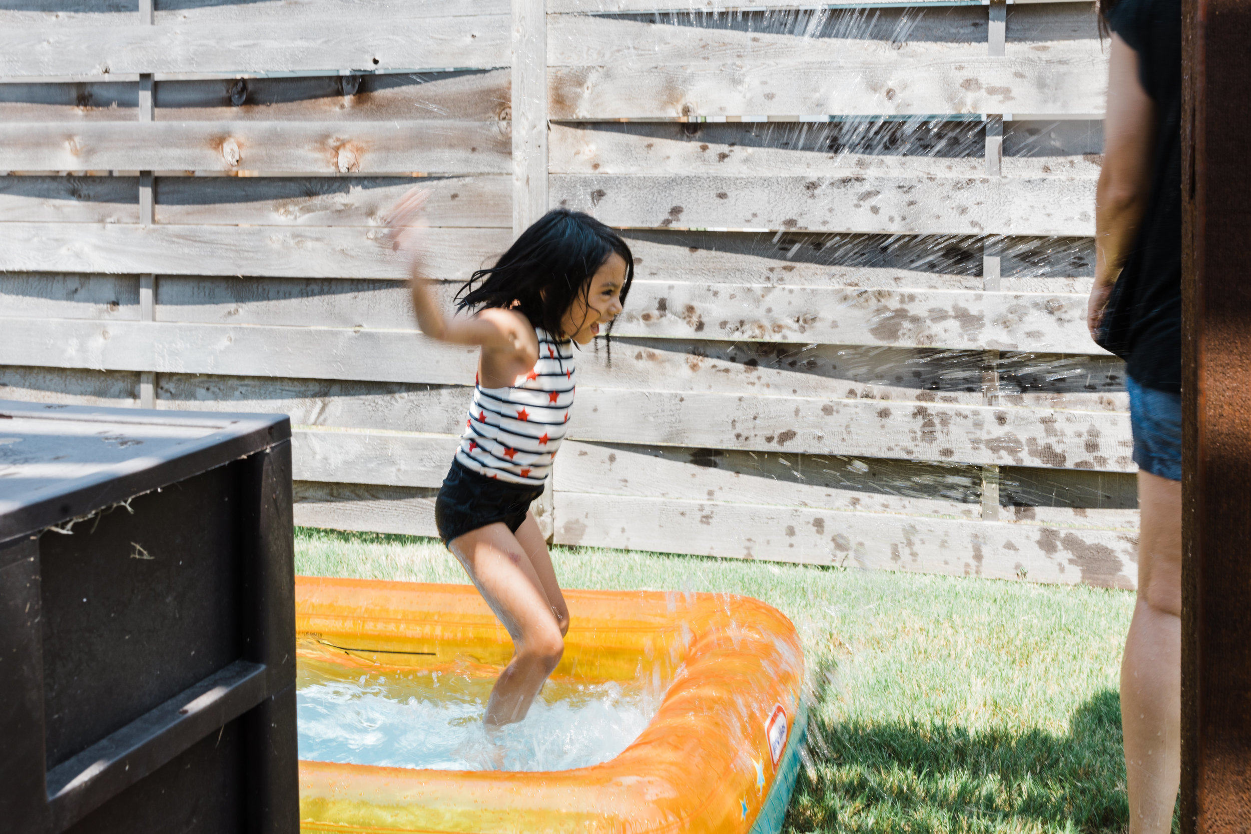 documentary lifestyle family photo session summer backyard girl jumping in pool Ore Adesina Photography Oklahoma City