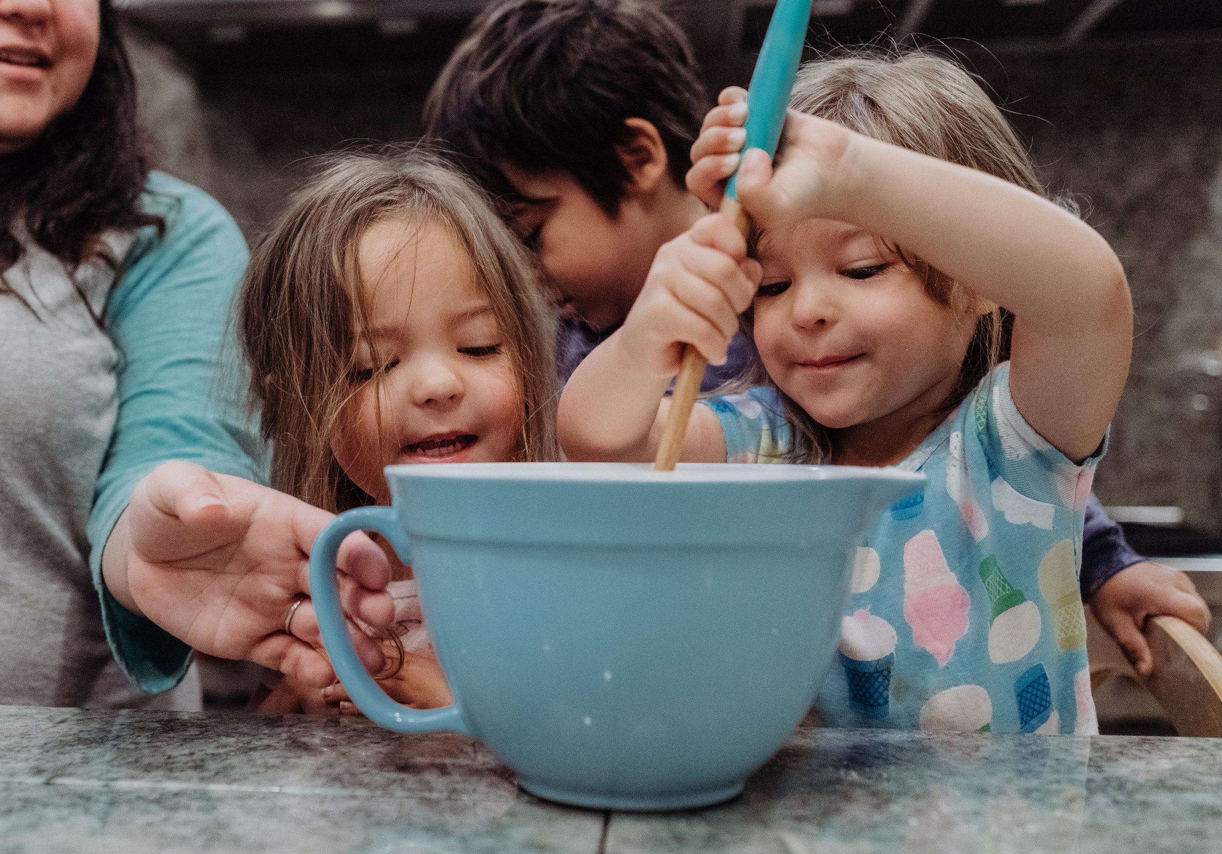 documentary lifestyle family photo session kids helping in kitchen mixing bowl Ore Adesina Photography Oklahoma City