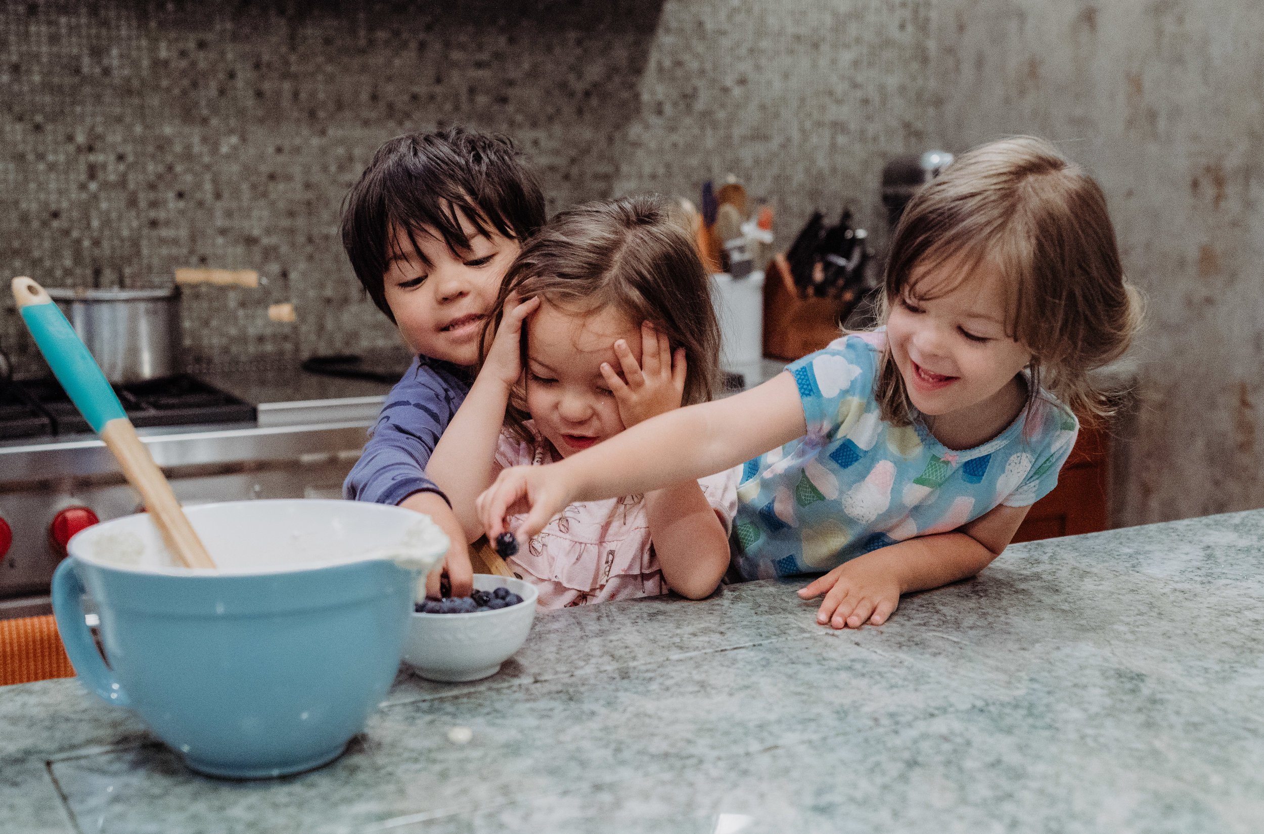 documentary lifestyle family photo session kids helping bake in kitchen mixing bowl Ore Adesina Photography Oklahoma City