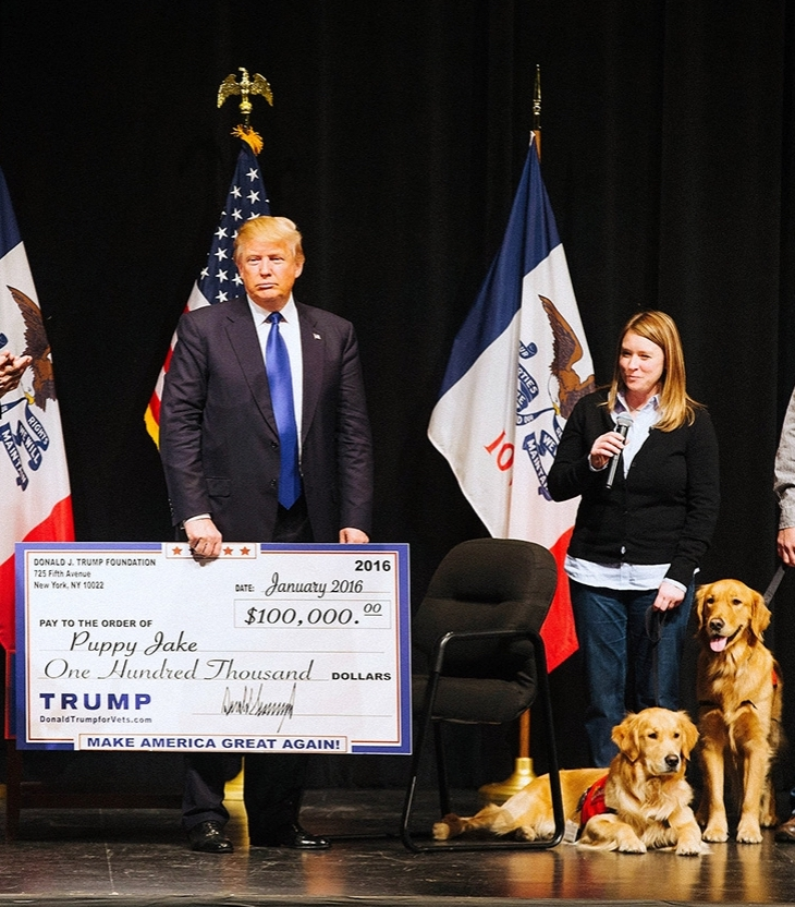 Donald Trump presents a check to the Puppy Jake Foundation while campaigning in Iowa in 2016 ( Image )