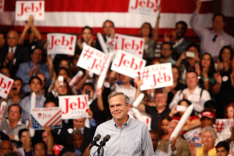 Then-candidate Jeb Bush in front of supporters boasting campaign signs ( Image )