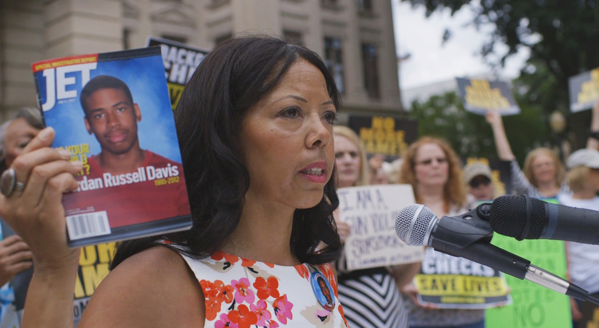McBath holding up a magazine with her son, Jordan Davis, on the cover ( Image )