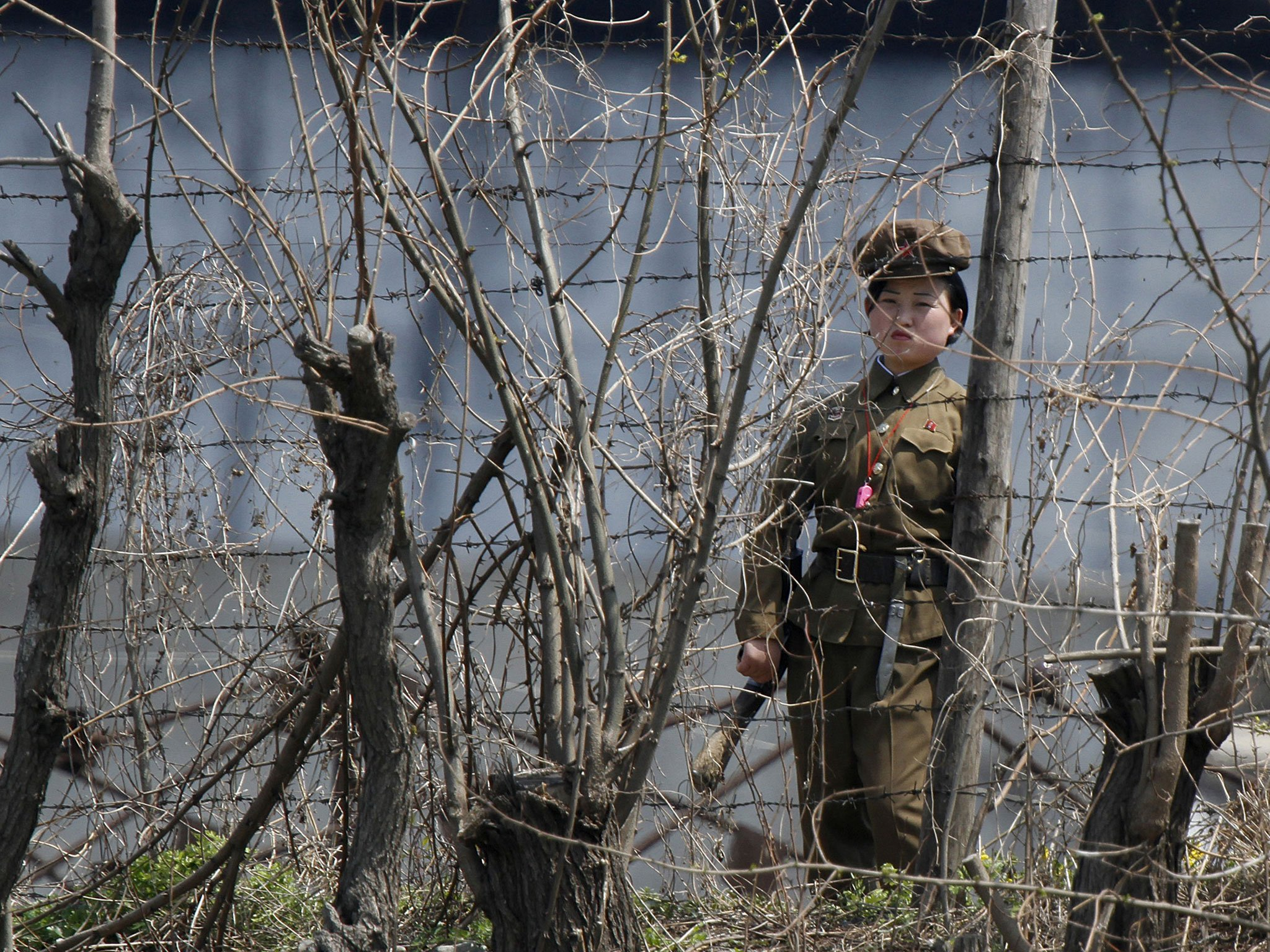 A North Korean policewoman on guard at a jail located on the Yalu River ( Image )