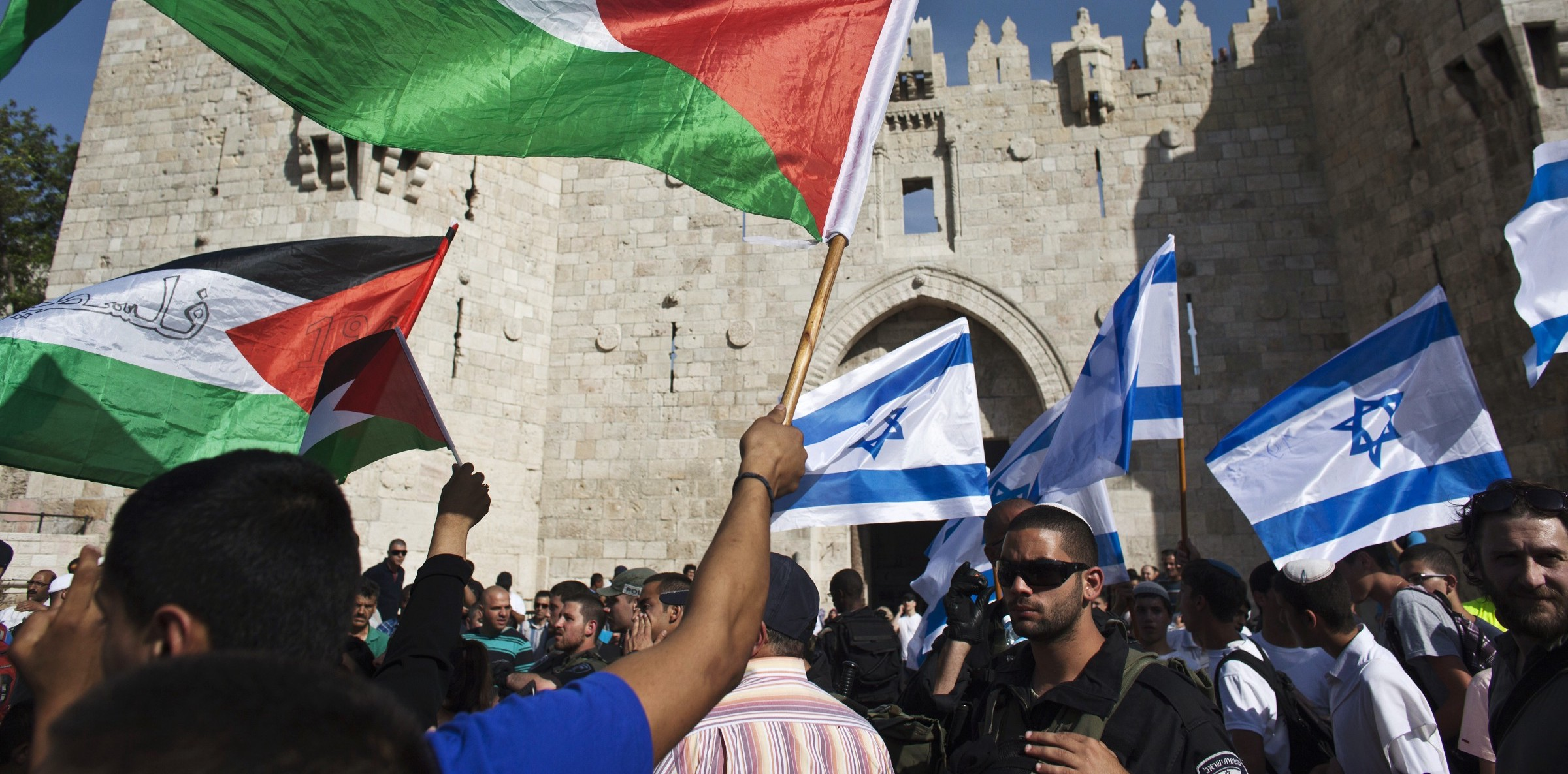 Israeli and Palestianian demonstrators waving the flags of their respective nations ( Image )