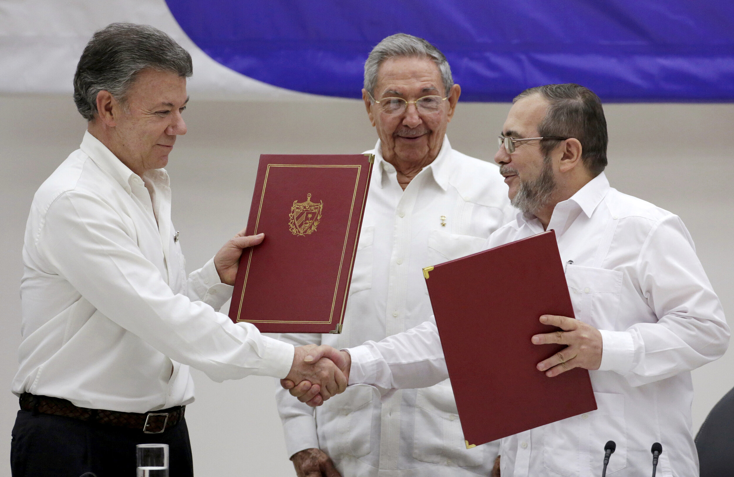 Former Colombian President Juan Manuel Santos (left) and FARC leader Rodrigo Londoño (right) signed a 2016 peace agreement overseen by former Cuban President Raul Castro (center) ( Image )