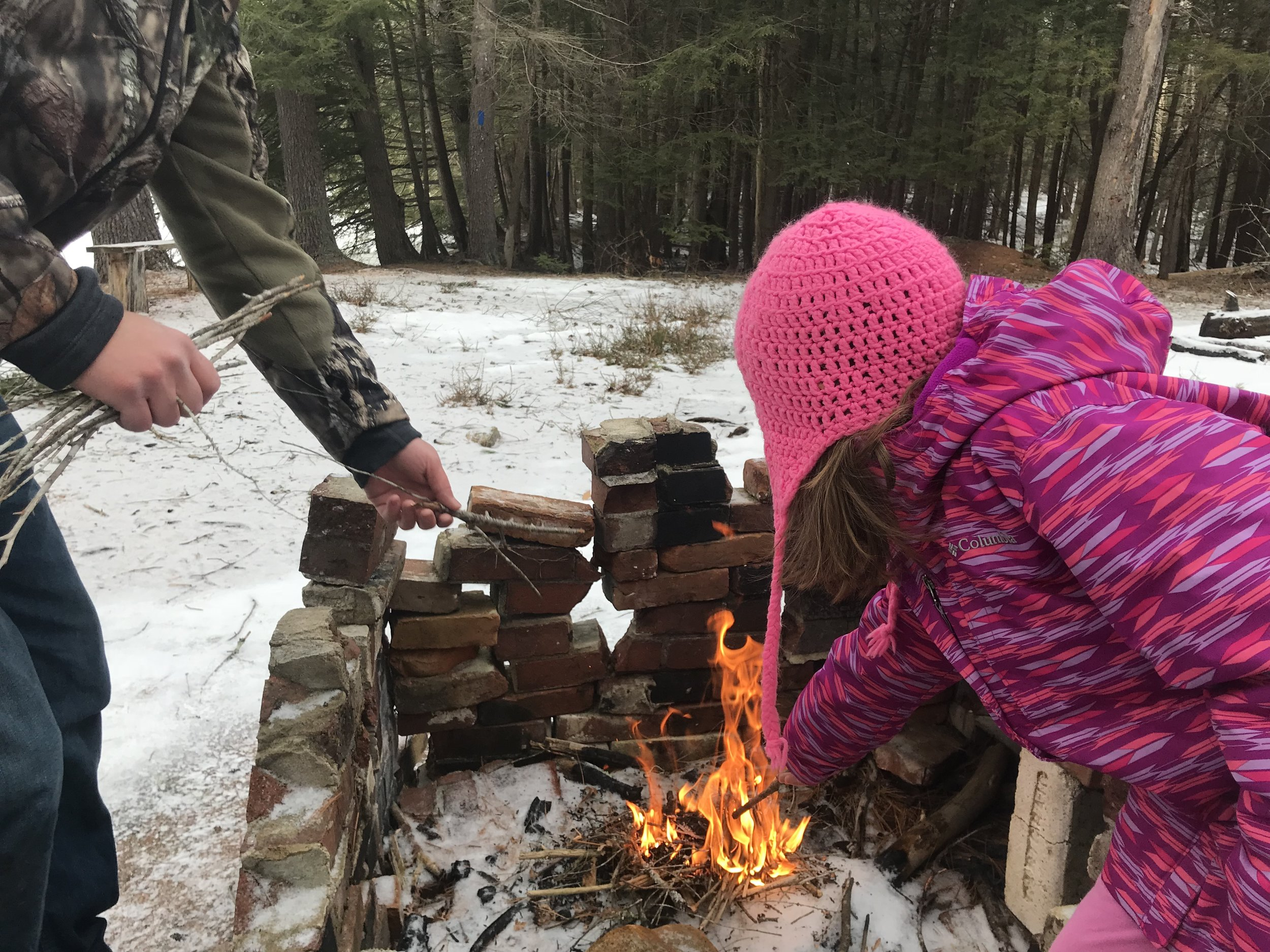 Working on our fire skills after a hike into the woods.