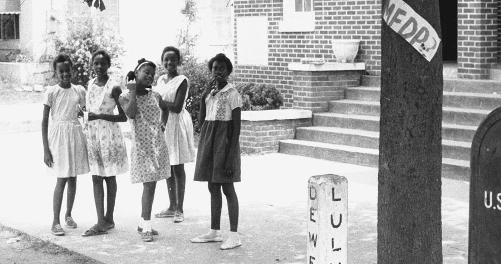Five African-American girls from Hattiesburg, Mississippi pose for the camera in front of True Light Baptist Church during Freedom Summer, 1964. They are (from left to right) Otis Ruth Travis, Veronica Carter, Glenda Polk, Dorothy Jean Patton, and Joyce McGowan. Affixed to the tree near the girls is a handmade sign for the Mississippi Freedom Democratic Party (MFDP). © 1964 Herbert Randal Freedom Summer Photographs, McCain Library and Archives, The University of Southern Mississippi.