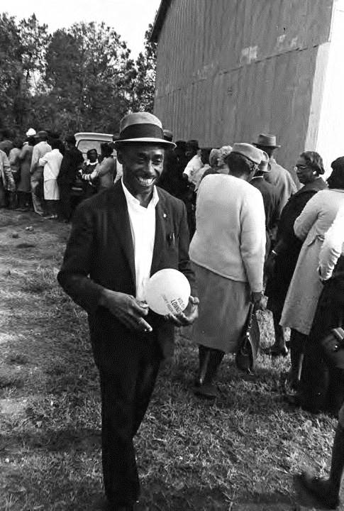 """Hulett is holding a balloon that reads, """"Vote Nov. 8 Lowndes County Freedom Organization."""" 1966. By Jim Peppler."""