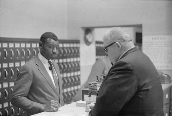 "Registrar Theron Lynd (right) finds one way or another to ""fail"" the Black applicants. Freedom Day, January 22, 1964, Hattiesburg. By Winifred Moncrief, from the MDAH."