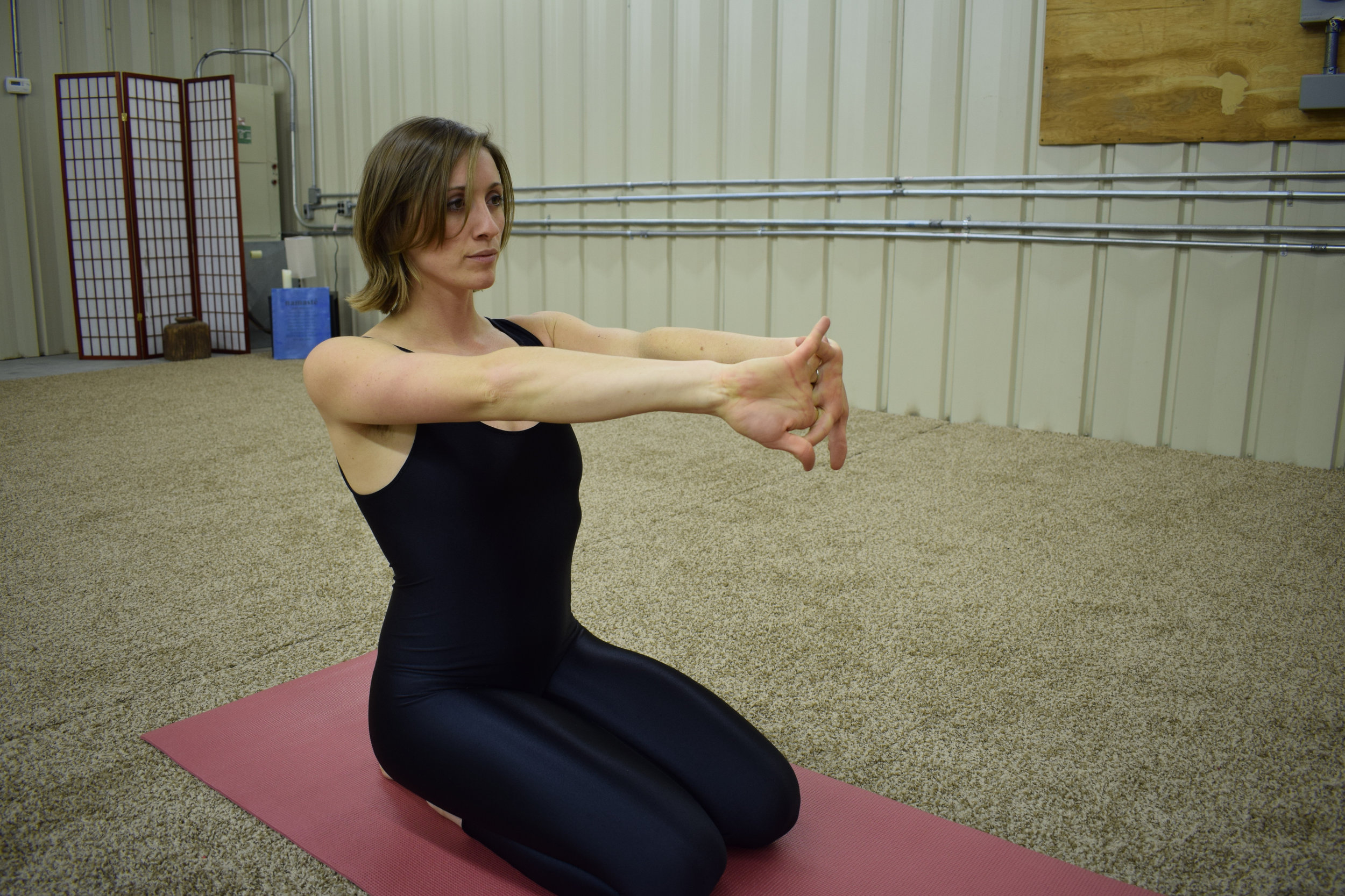 Figure 4: Interlace fingers, lock the shoulders back, and extend through the palms facing outward sending energy to the hands and wrists. Gaze softly in front of you.