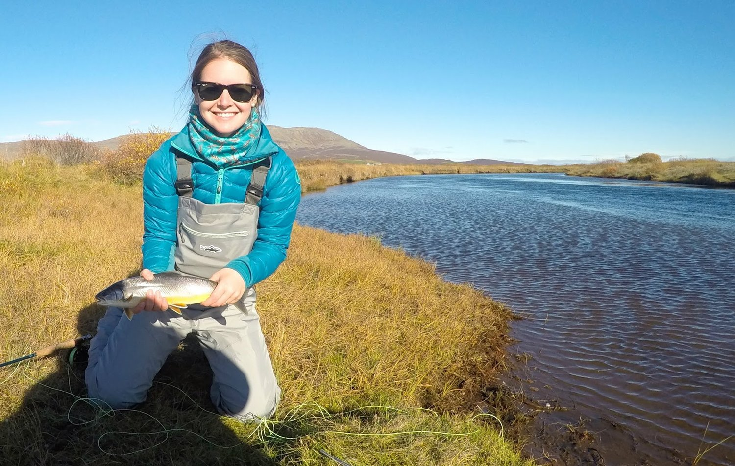 Me with an Arctic Char in Iceland. Wearing waders and a down jacket and neck warmer.