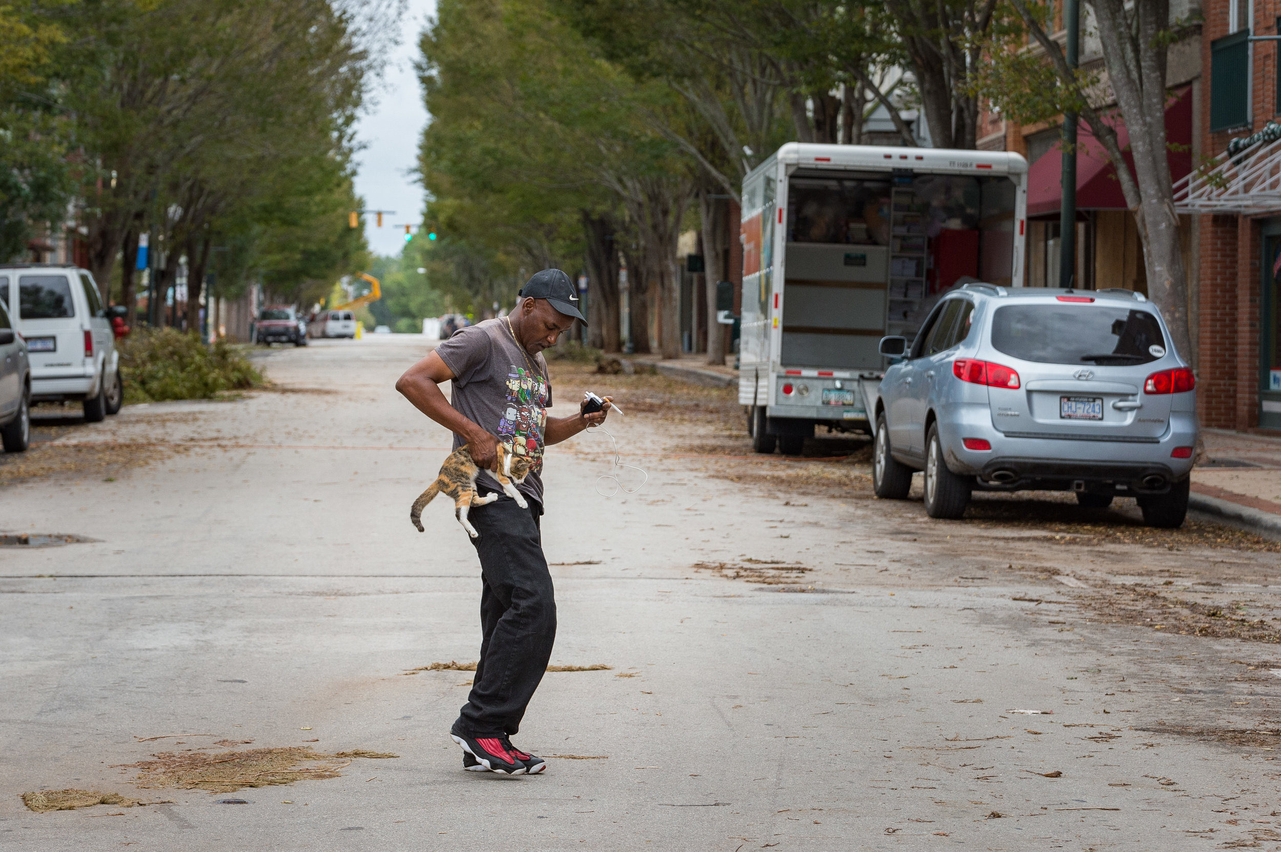 September 16, 2018, New Bern, NC- After flood waters receded in New Bern, a man is seen walking in the downtown area with his kitten.