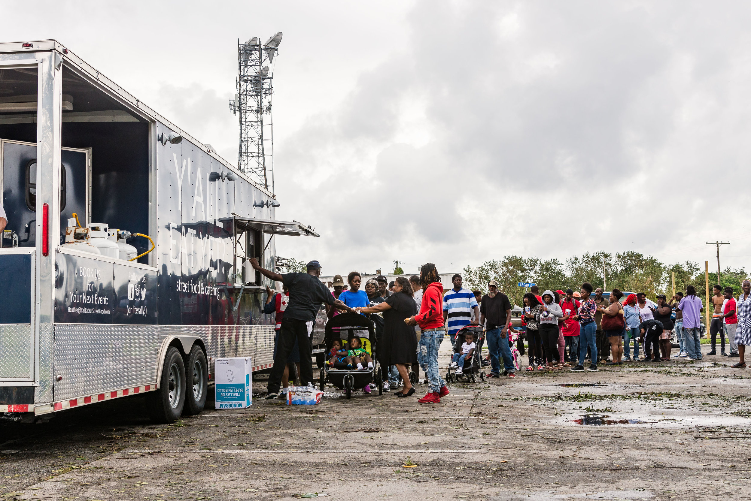 """September 16, 2018, New Bern, NC- New Bern residents line up to receive meals from food truck vendor """"Y'All Eat Yet"""" and the American Red Cross in the parking lot of Trinity Chapel AME Zion Church at Cawford Street and Broad Street in the aftermath of Hurricane Florence."""