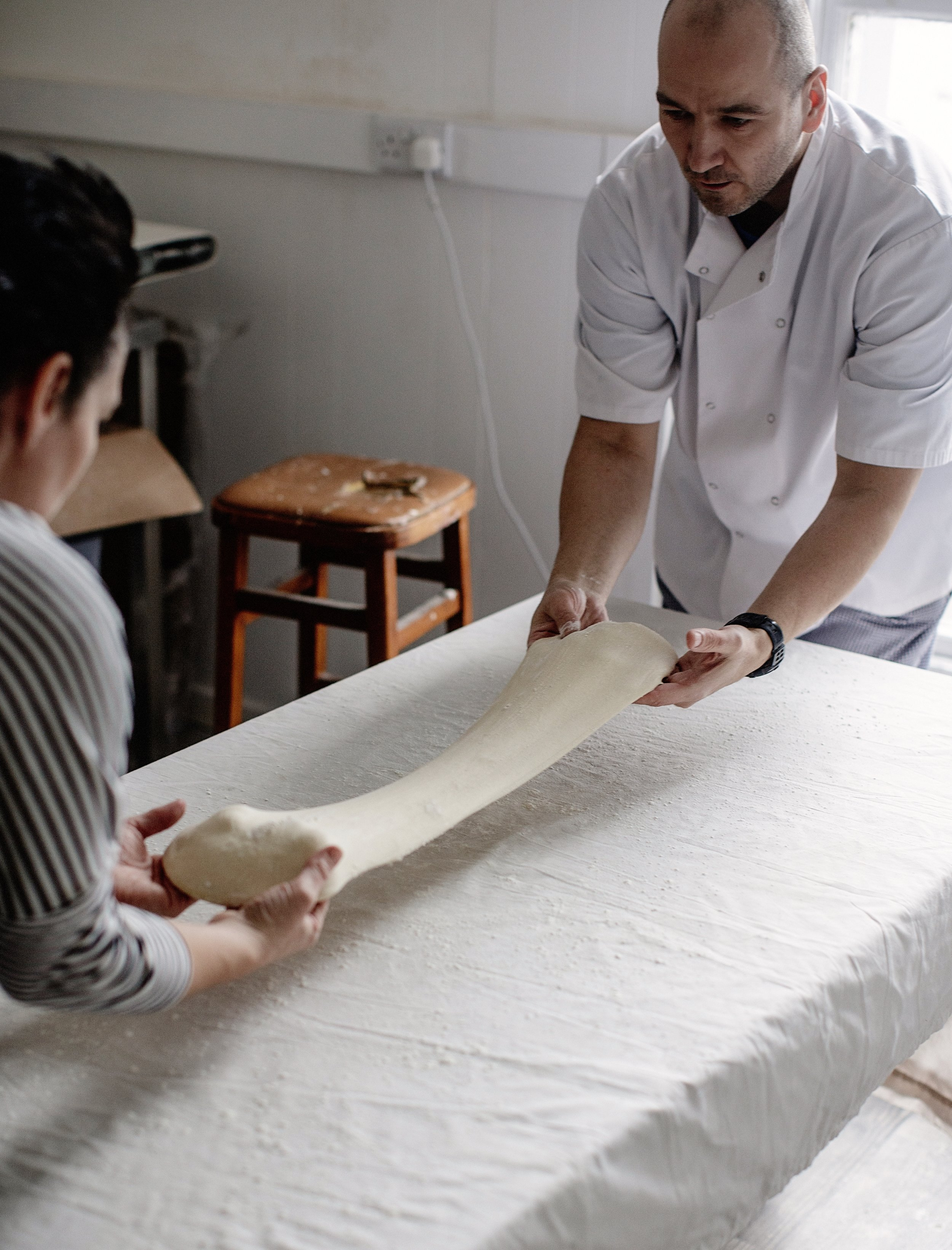 Stretching the dough is a two-person job.
