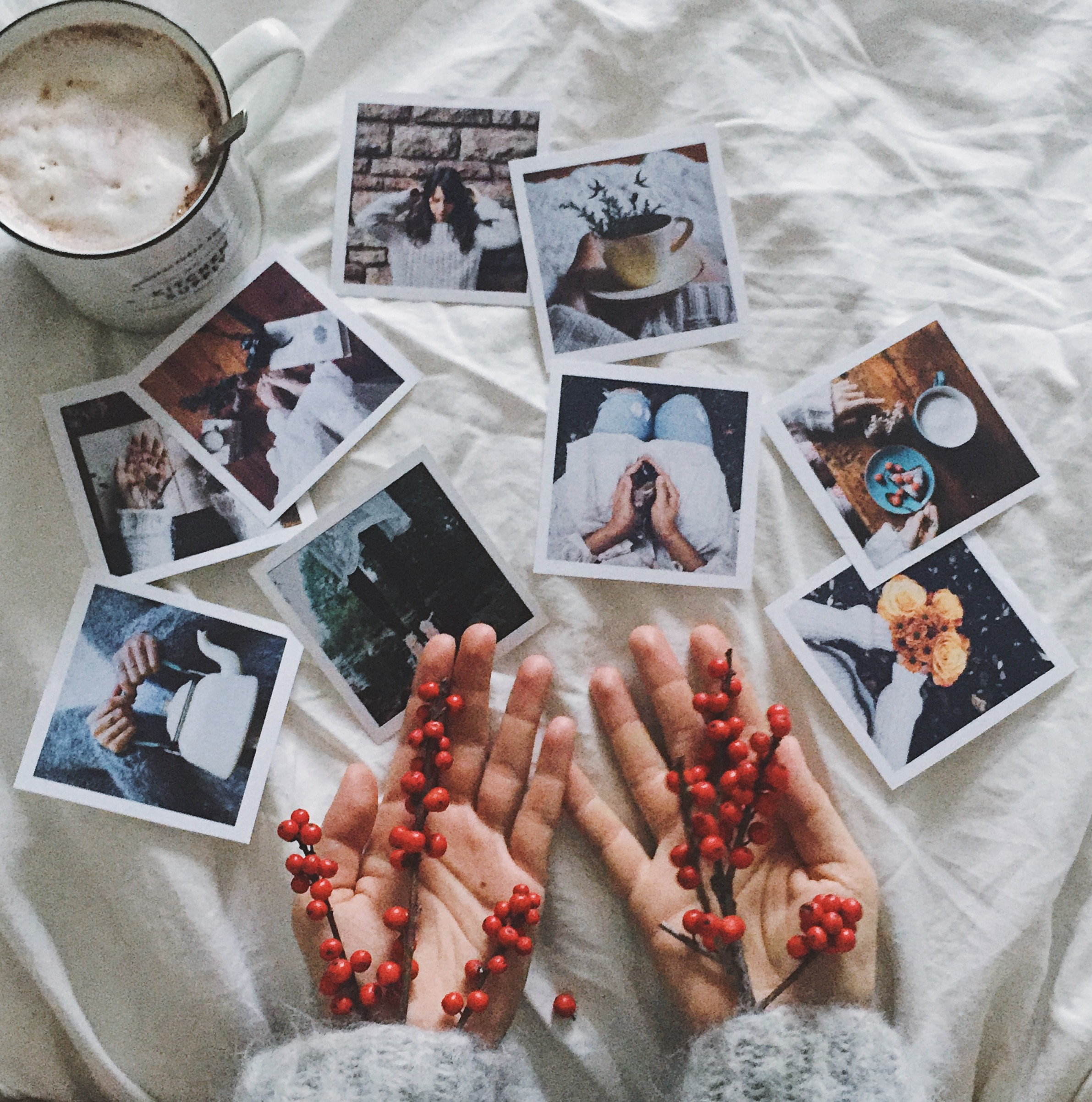 Coffe cups and polaroid pictures in bed