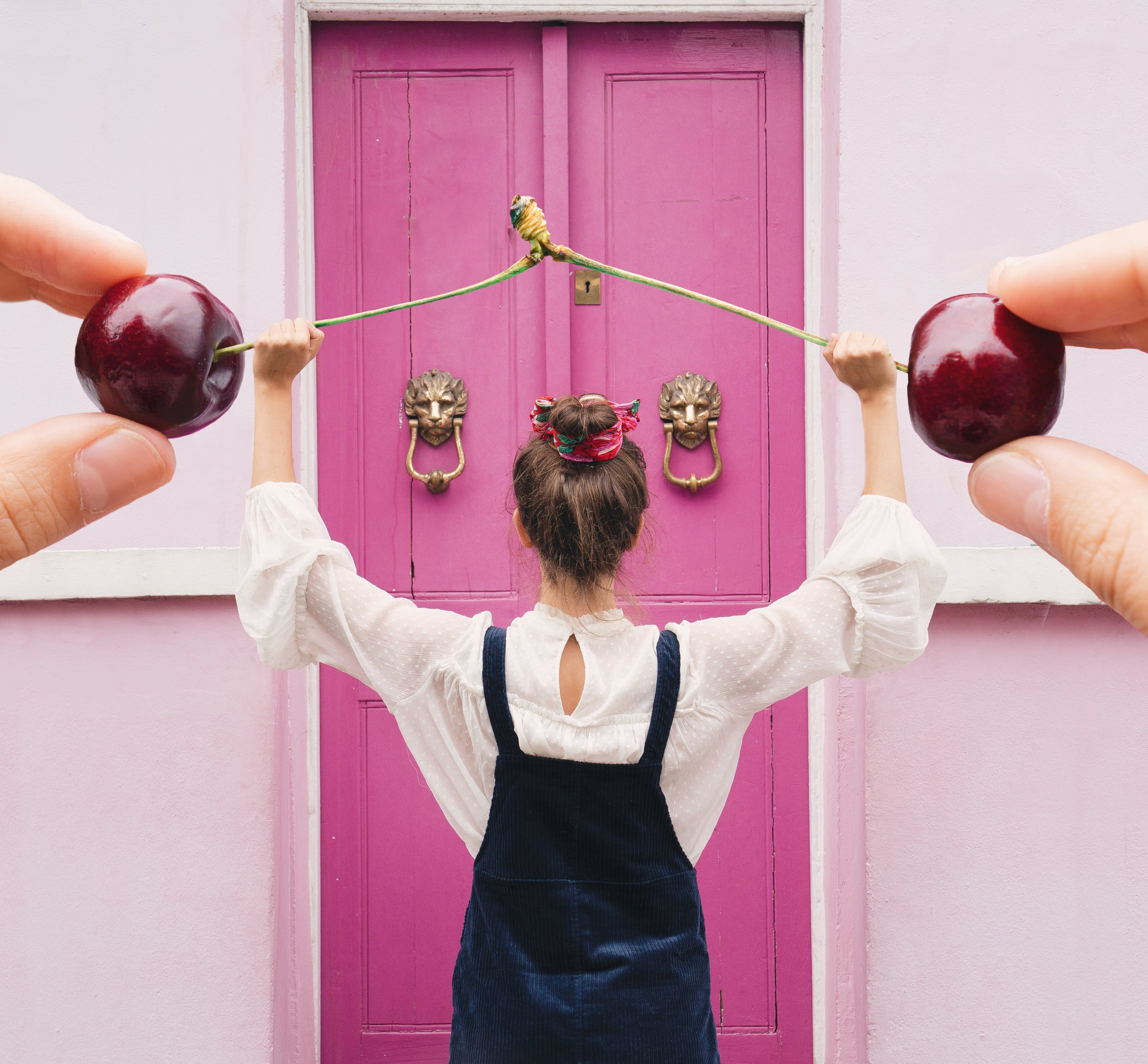 Thinsg I'm excited about for fall-Standing in front of a pink door in Notting Hill with forced perspective cherry power bar