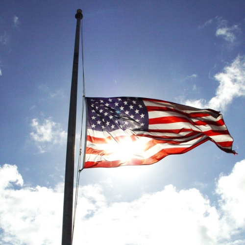 The US flag flies at half-mast, honoring the military lives lost.