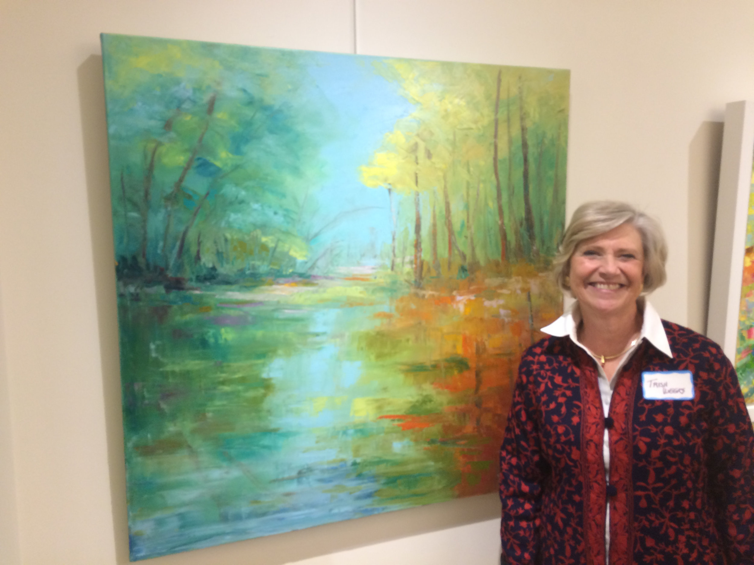 Cincinnati artist Trish Weeks standing in front of her abstract painting at the YWCA