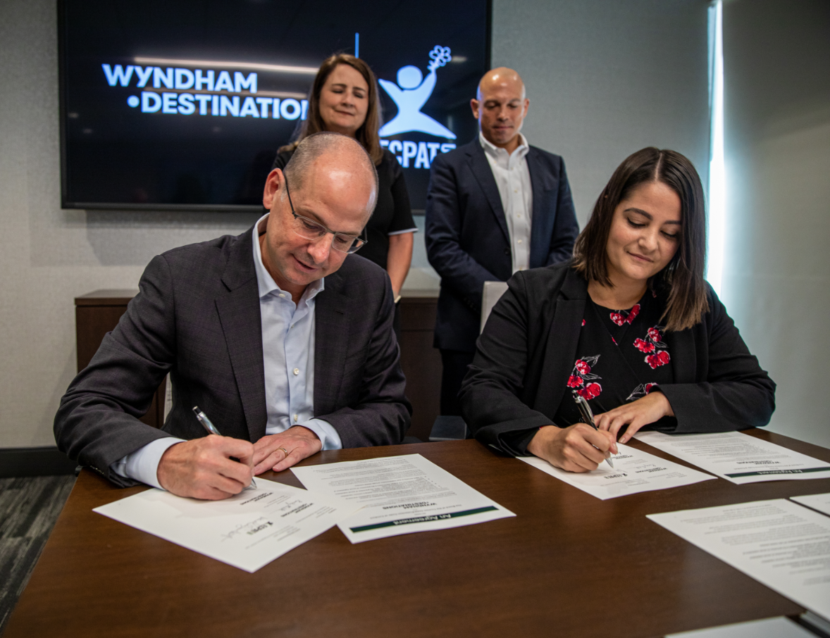Michael D. Brown President & Chief Executive Officer (CEO) for Wyndham Destinations, left, and Michelle Guelbart sign The Code.