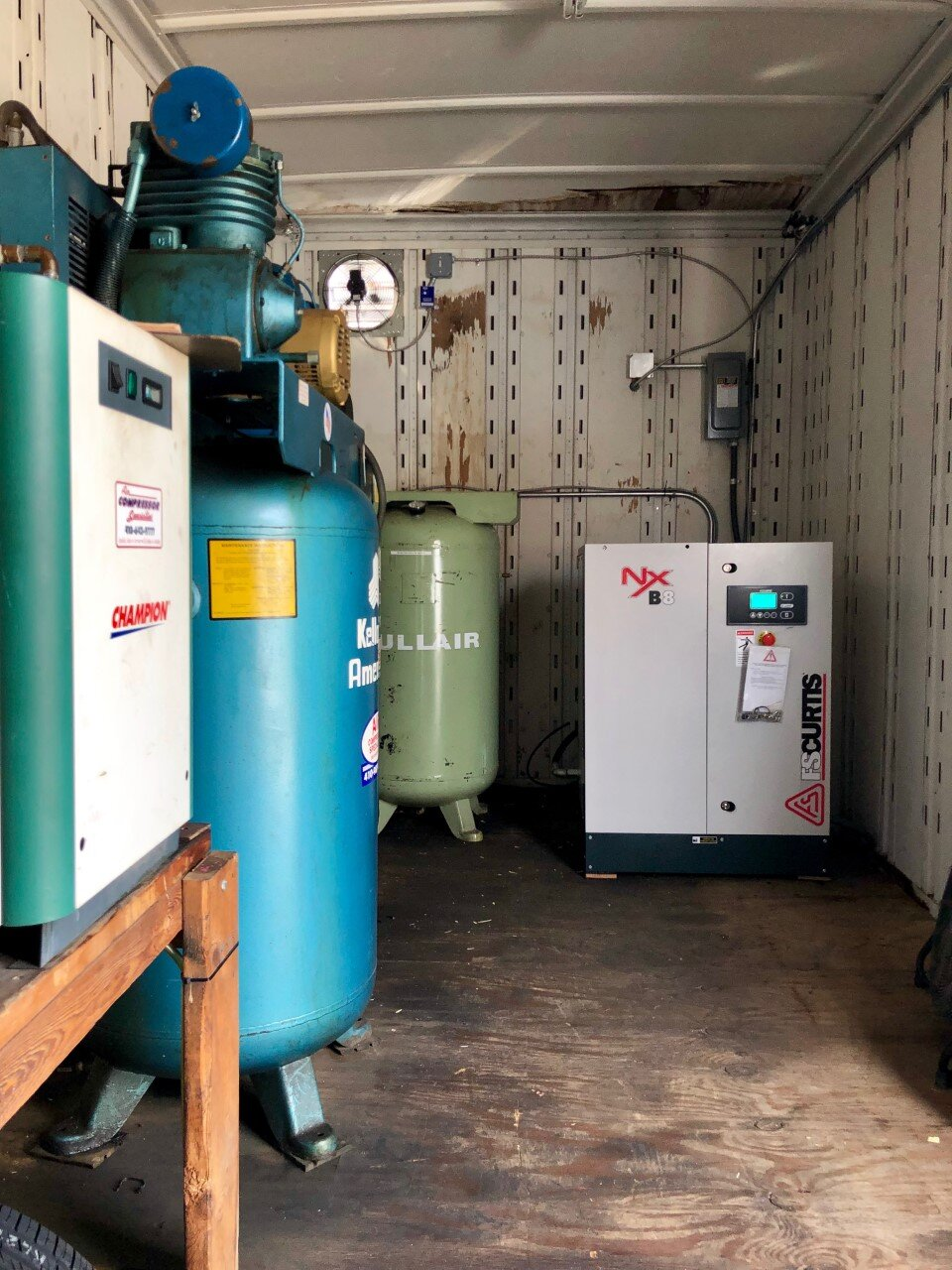 New 10 HP FS-Curtis Nx rotary screw compressor installed along with a Kellogg reciprocating compressor and a Champion refrigerated air dryer at an automotive shop