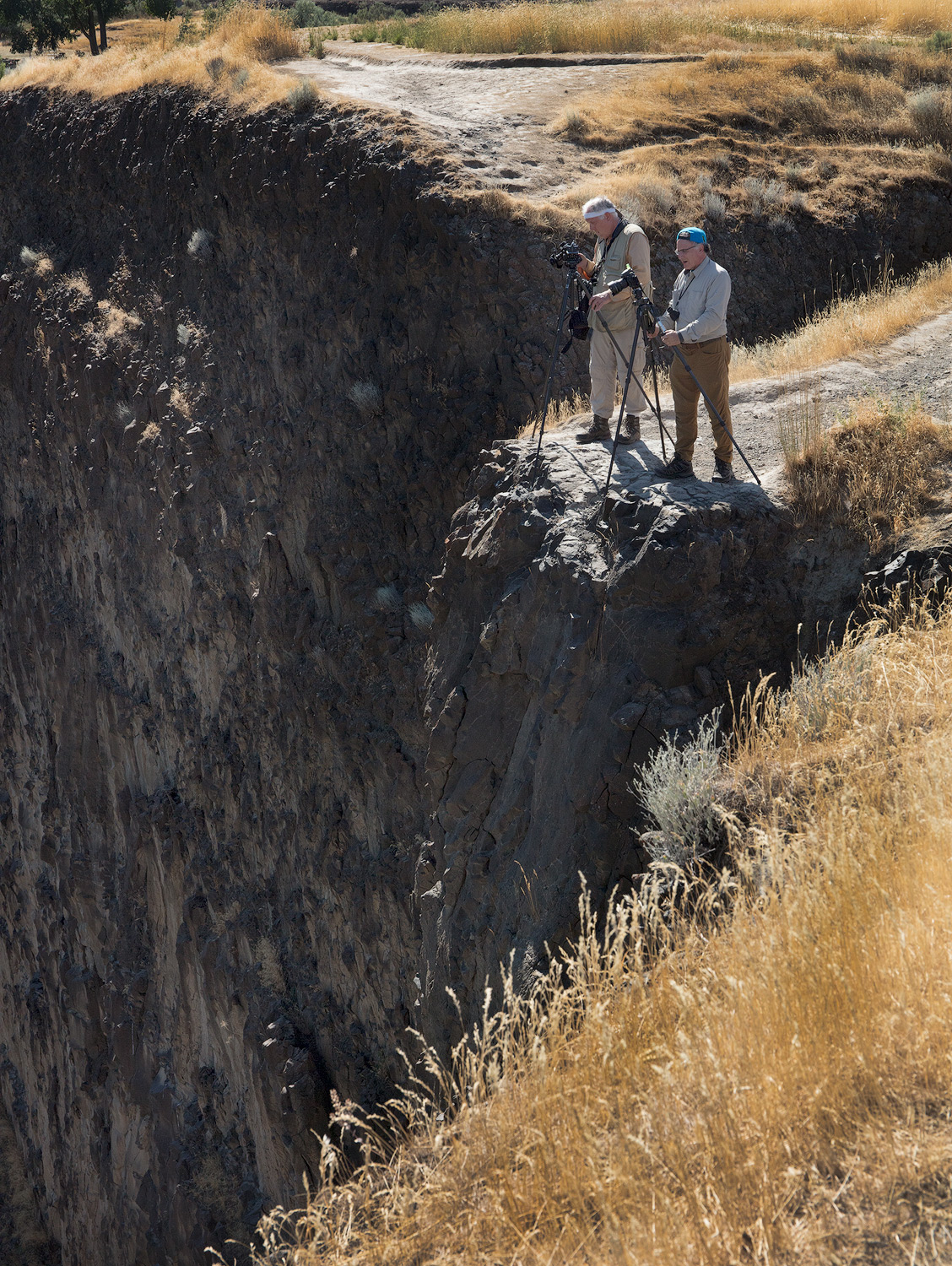 Photographers lining up a shot of Palouse Falls from the edge of the ravine.