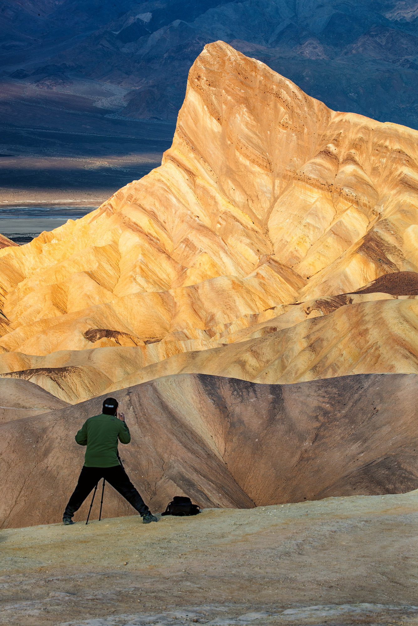 A photographer frames up a shot, taking advantage of the beautiful early morning light at Zabriskie Point in Death Valley National Park, California. February, 2018